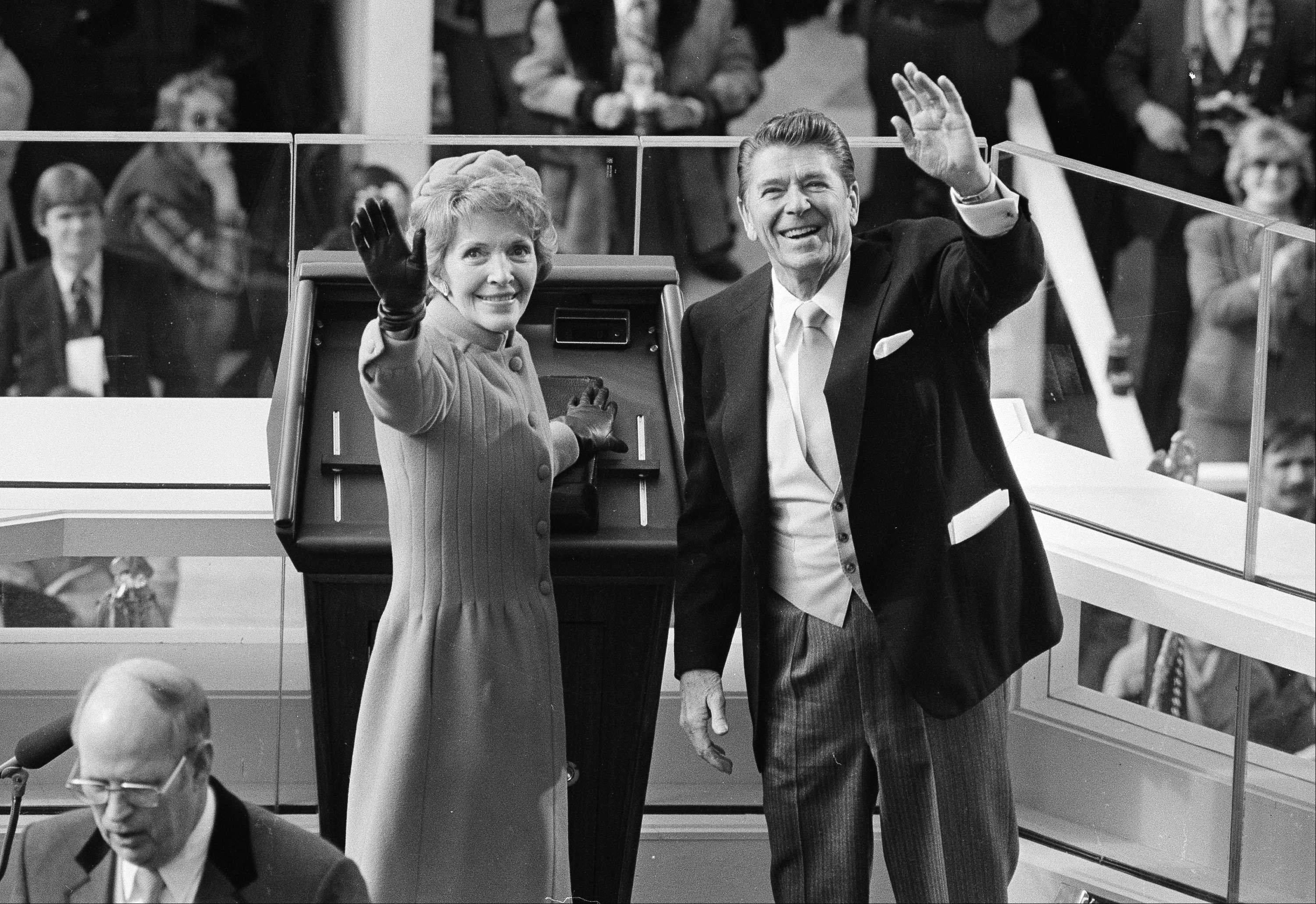 President Ronald Reagan and first lady Nancy Reagan wave to onlookers at the Capitol building as they stand at the podium in Washington following the swearing in ceremony, Jan. 20, 1981.