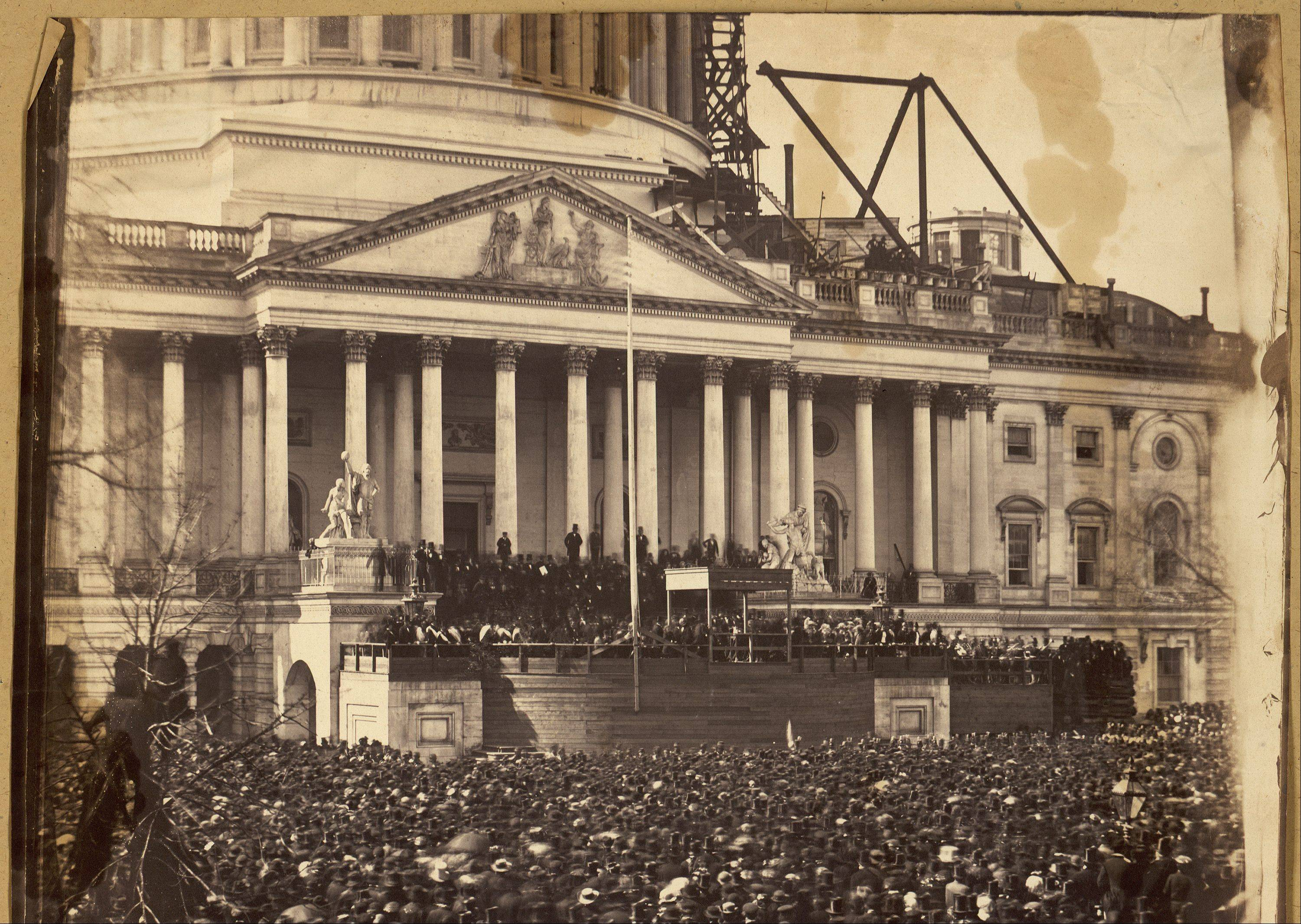 In this photo provided by the Library of Congress, participants crowd around at the first inauguration of President Abraham Lincoln at the U.S. Capitol in Washington, D.C., on March 4, 1861. Lincoln is standing under the wood canopy, at the front, midway between the left and center posts. His face is in shadow but the white shirt front is visible.