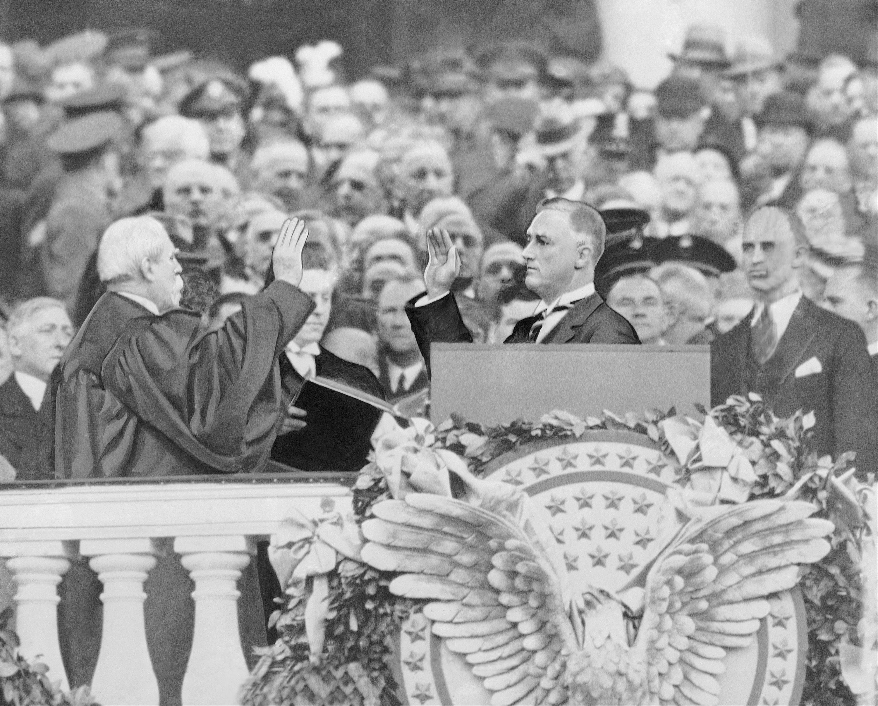 Franklin Delano Roosevelt takes the oath of office as the 32nd president of the United States from Chief Justice Charles Evans Hughes, March 4, 1933.