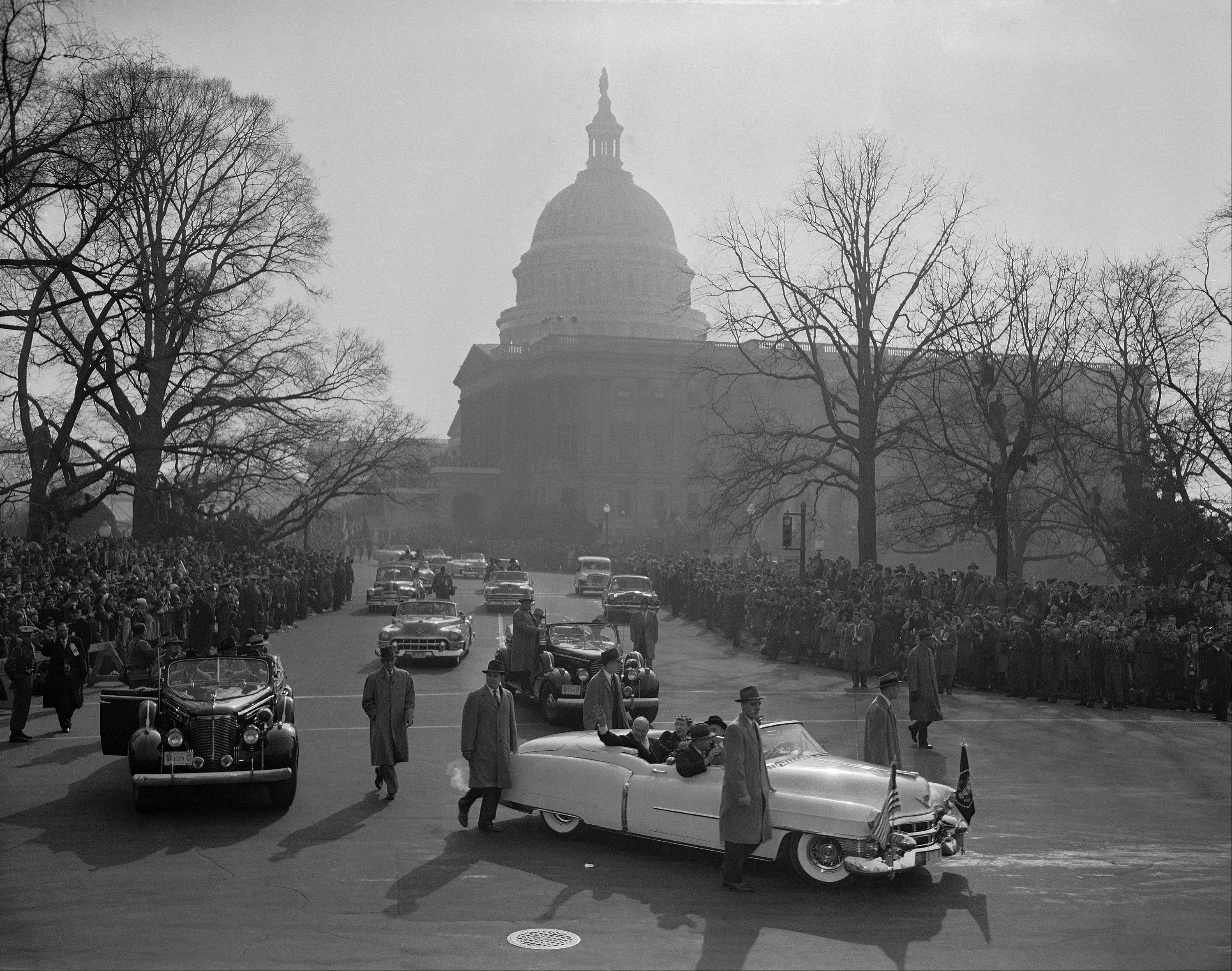 Riding in open a car, the Dwight Eisenhower lead inaugural parade from Capital grounds after the swearing in ceremonies in Washington, Jan. 20, 1953. Ike waves as car turns onto Constitution Avenue. In background is Capitol dome.