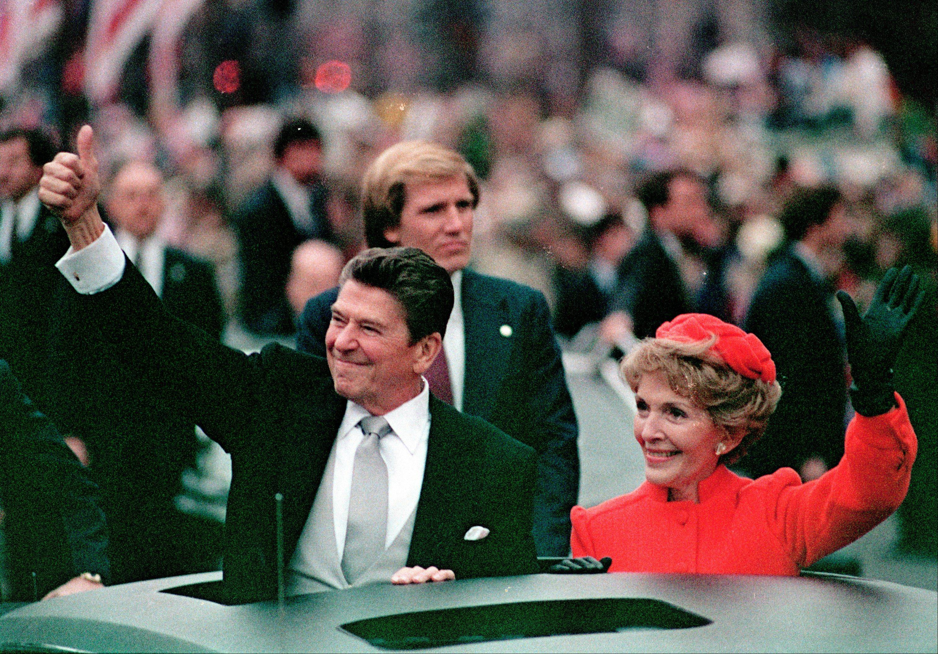 U.S. President Ronald Reagan gives a thumbs up sign to the crowd as his wife, first lady Nancy Reagan, waves from limousine during the inaugural parade in Washington, D.C., Jan. 20, 1981.