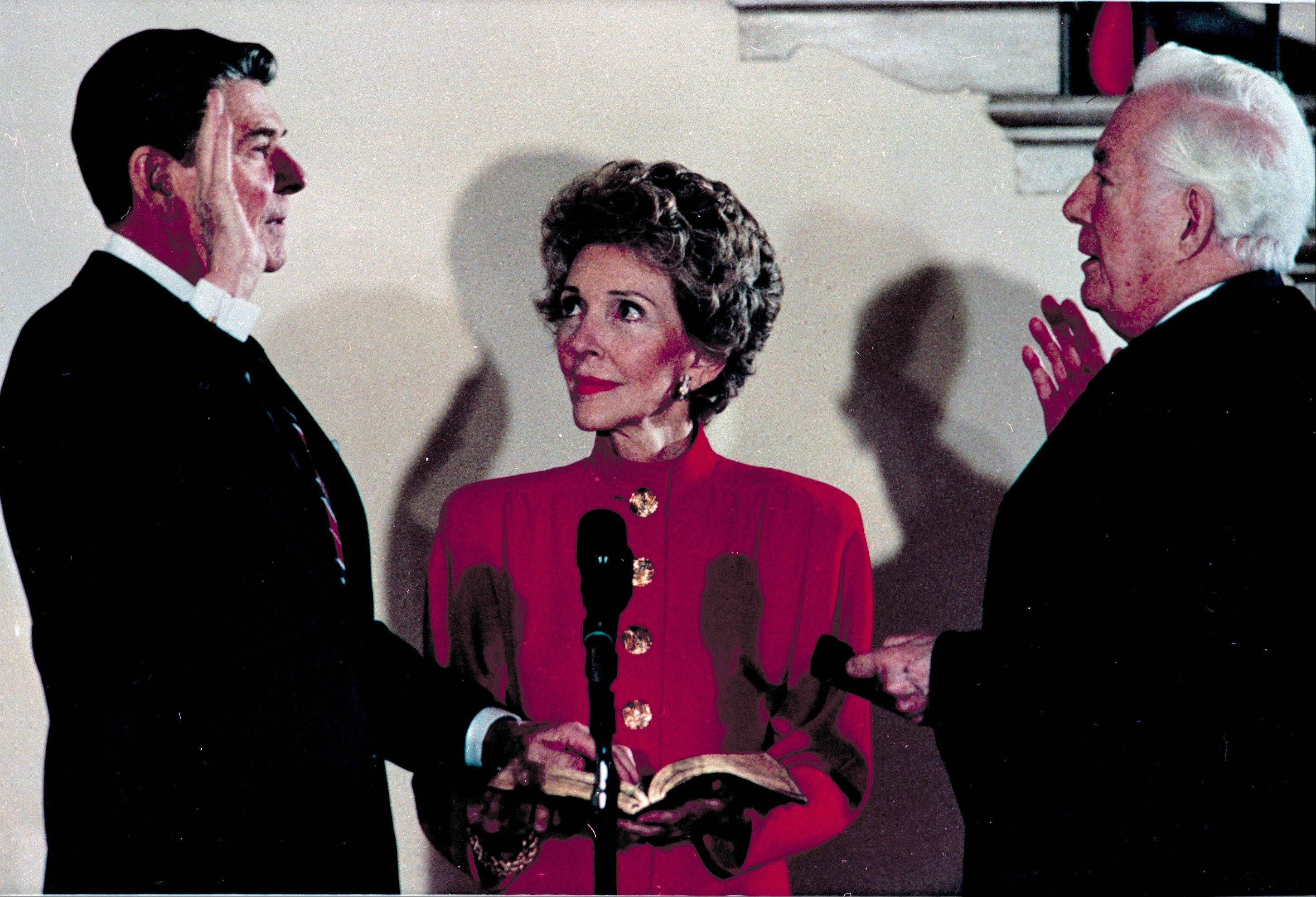 President Ronald Reagan takes the oath of office administered by Chief Justice Warren Burger in a private White House ceremony for a second term in Washington, D.C., Sunday, Jan. 20, 1985. First Lady Nancy Reagan holds the bible.