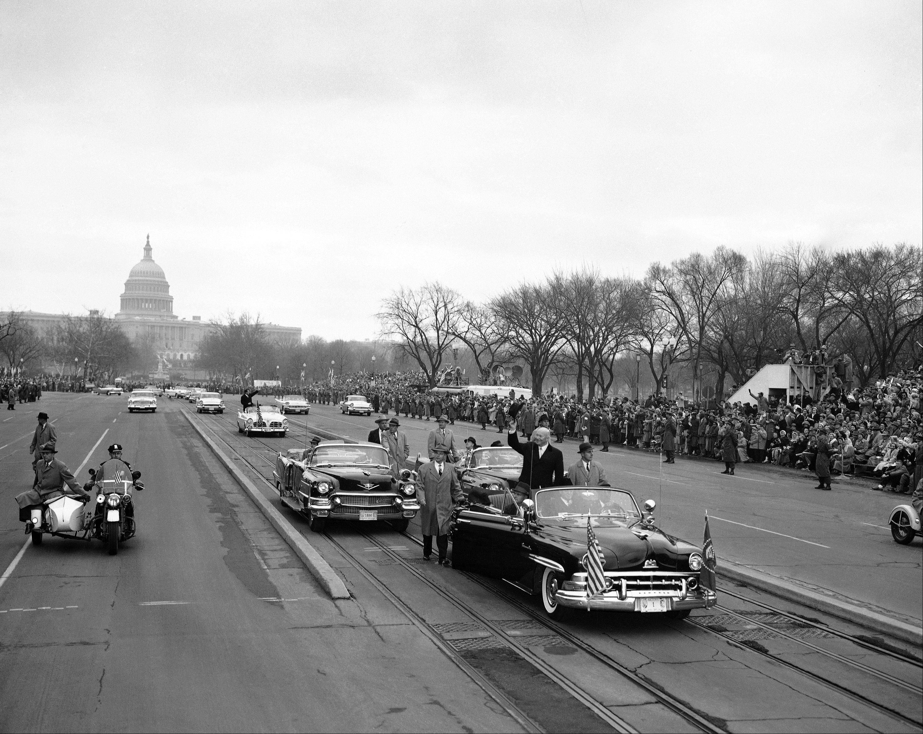 President Dwight Eisenhower stands in his open car and waves as he leaves the Capitol just before swinging into Constitution Avenue on traditional inaugural parade route in Washington on Jan. 21, 1957.
