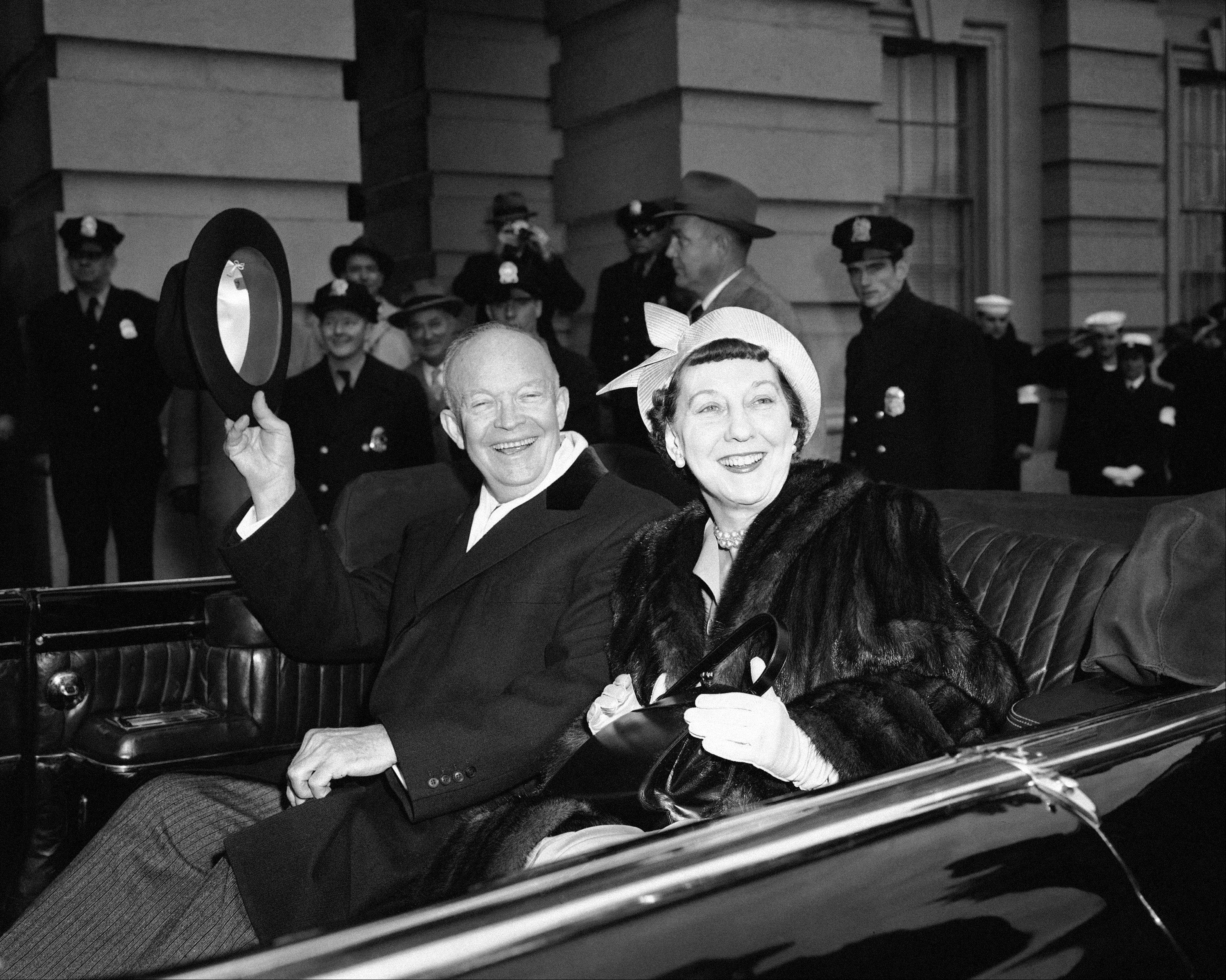 President Dwight Eisenhower and Mrs Mamie Eisenhower sit in the open car and wave as they leave the Capitol in Washington Jan. 21, 1957, just before swinging into Constitution Avenue on traditional inaugural parade route.