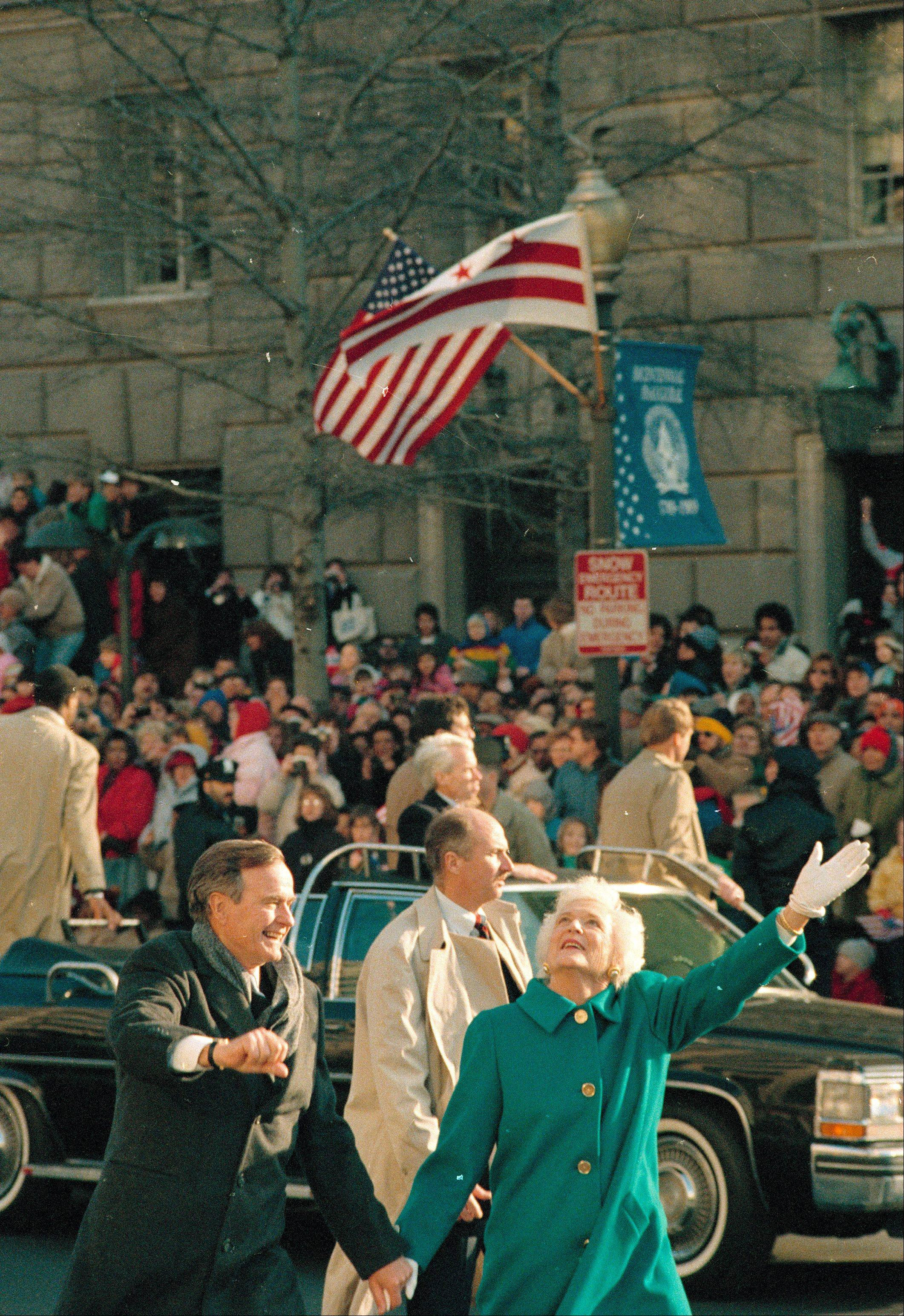 President George Bush, left, and his wife, first lady Barbara Bush, wave to the crowd on Pennsylvania Avenue after getting out of their limousine and walking the inaugural parade route in Washington, D.C., Friday, Jan. 20, 1989.