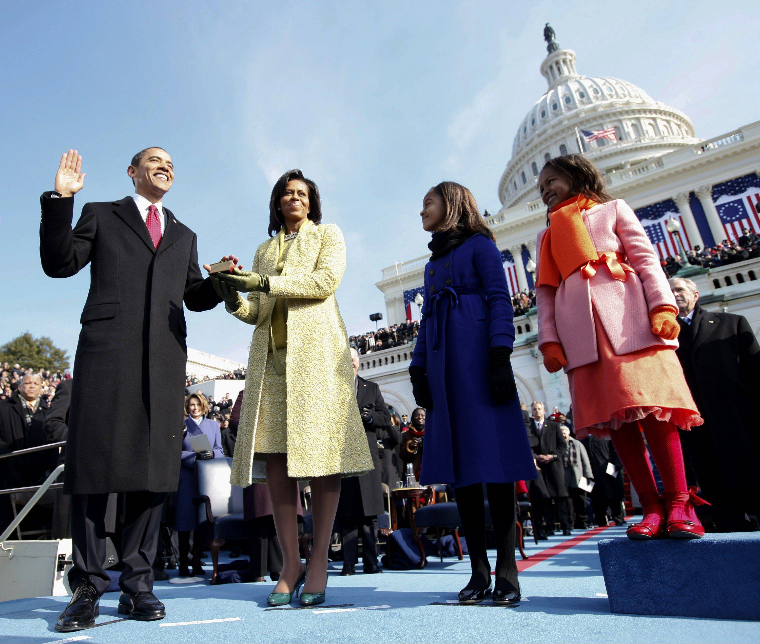 Barack Obama, left, takes the oath of office from Chief Justice John Roberts, not seen, as his wife Michelle, holds the Lincoln Bible and daughters Sasha, right and Malia, watch at the U.S. Capitol in Washington, Tuesday, Jan. 20, 2009.