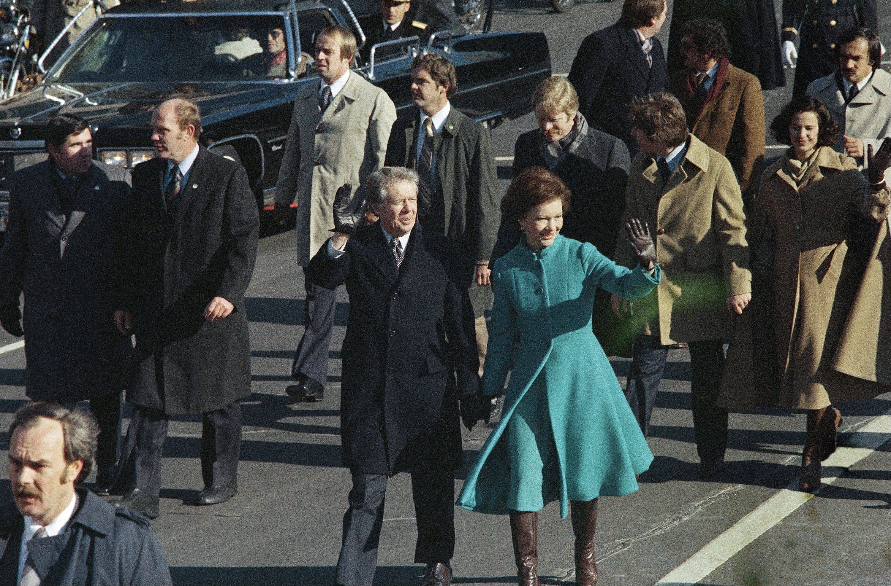 This Jan. 20, 1977 file photo shows President Jimmy Carter and First Lady Rosalynn Carter waving as they walk down Pennsylvania Avenue .At some point on Inauguration Day, if all goes expected, the president's limousine will slow to a stop on its journey down Pennsylvania Avenue from the Capitol to the White House. In that moment, Pennsylvania Avenue is America's red carpet. And the president is the only celebrity on it. The victory walk has become an iconic inaugural moment, a tradition dates only to President Jimmy Carter.