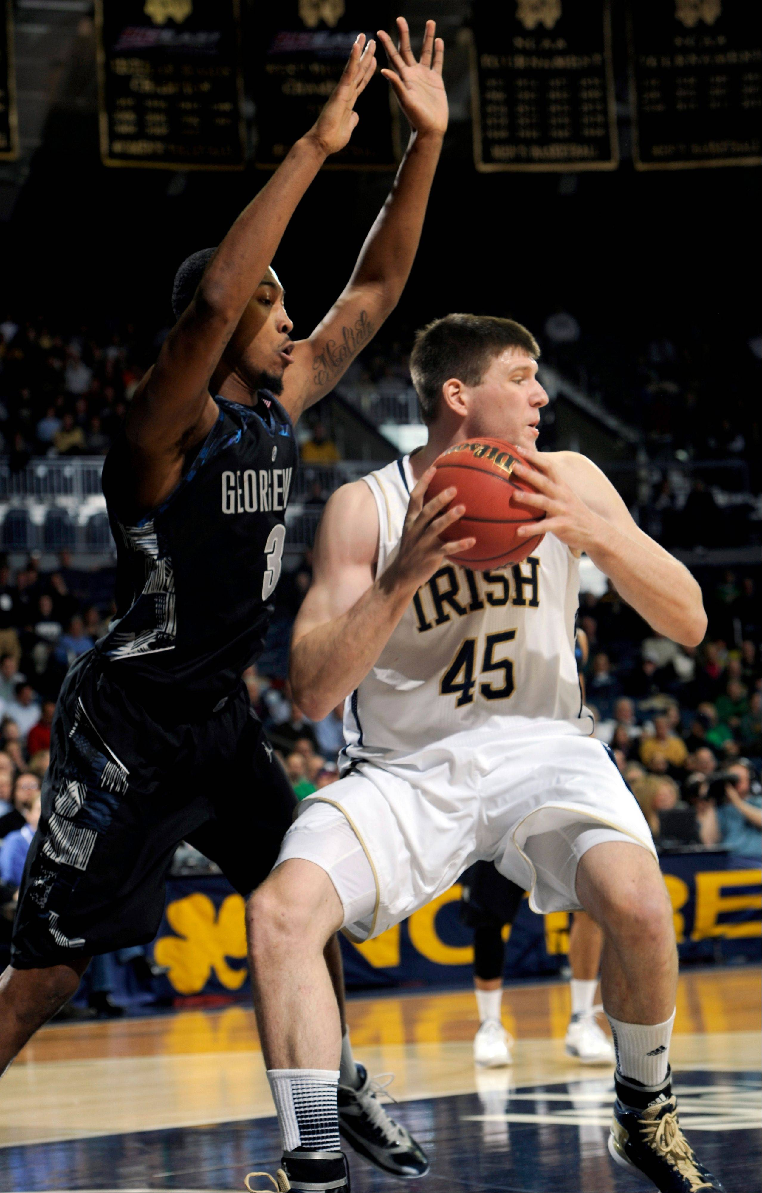Notre Dame forward Jack Cooley, right, tries to drive the lane as Georgetown forward Mikael Hopkins defends during the first half of an NCAA college basketball game, Monday Jan. 21, 2013, in South Bend, Ind.