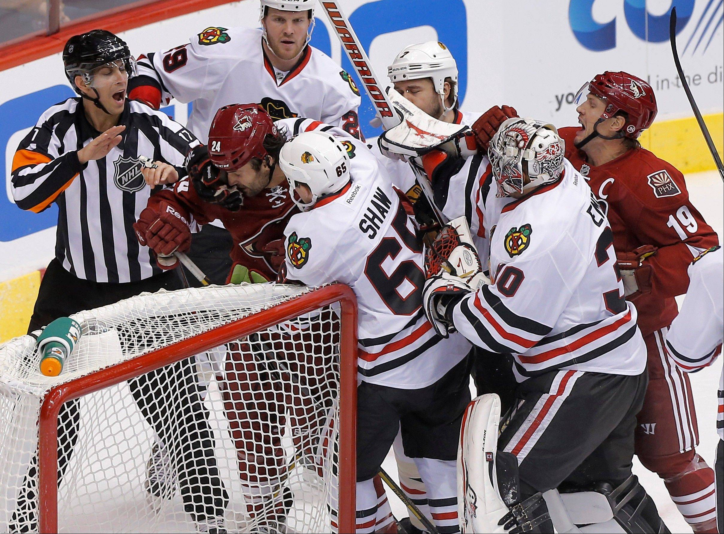 Phoenix Coyotes' Kyle Chipchura (24) and Blackhawks winger Andrew Shaw (62) are seperated by teammates and an official during a fight in the second period Sunday.