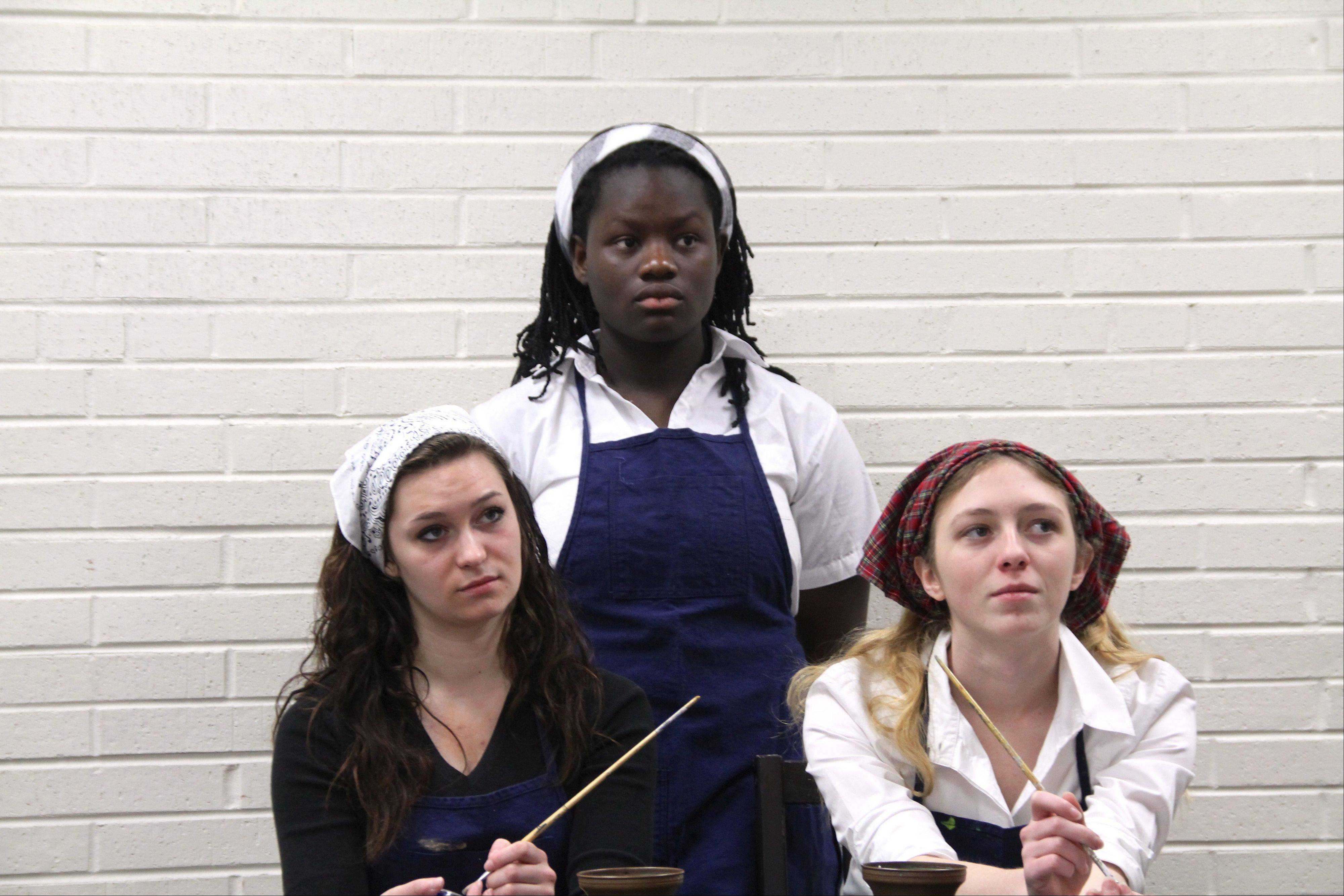 Mundelein High School students, from left, Liz Grein, Jerra Whapoe and Maya St. Clair rehearse the school�s upcoming play, �Radium Girls,� which opens Jan. 31.