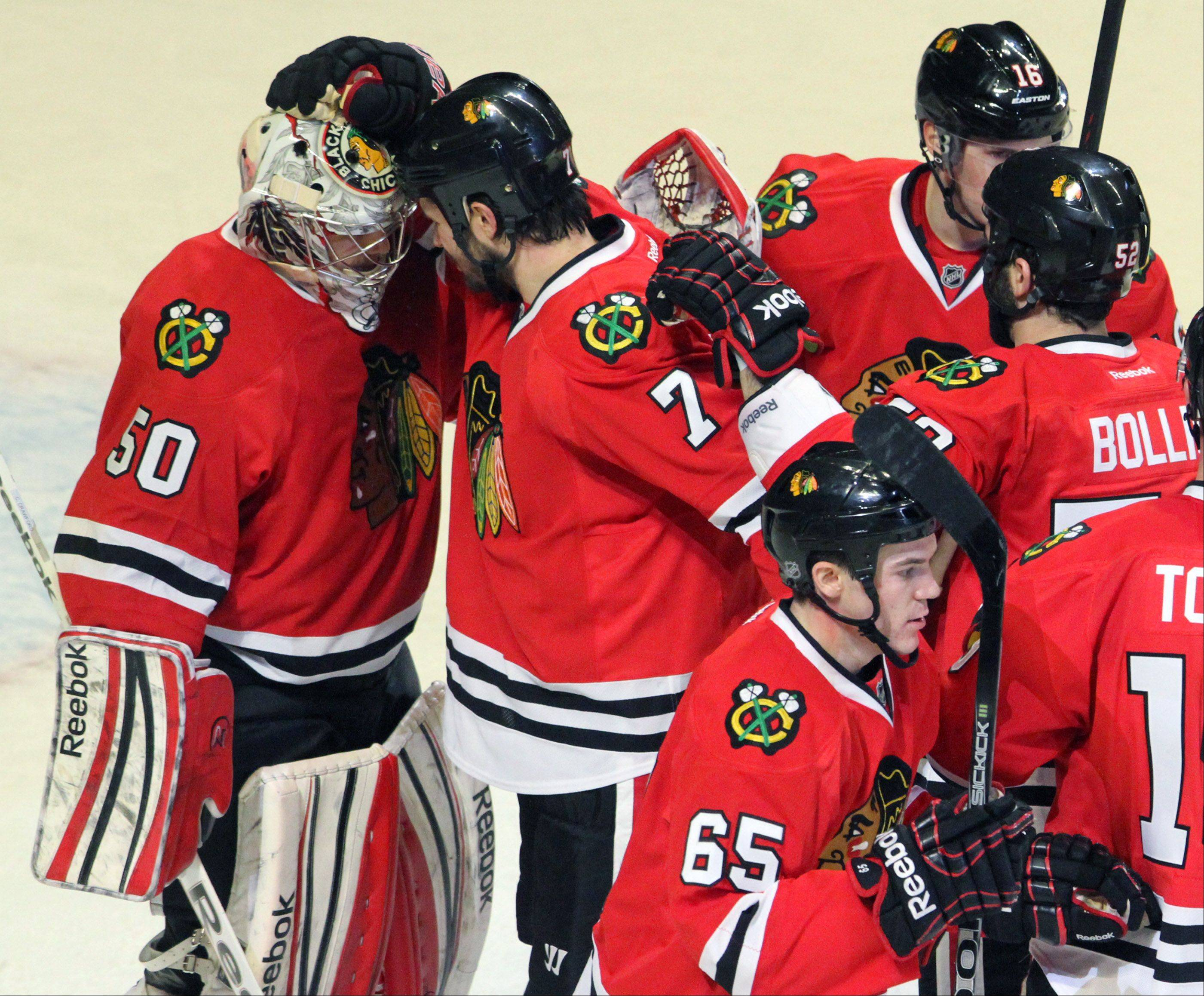Blackhawks defenseman Brent Seabrook gives goalie Corey Crawford a hand after the Hawks� 3-2 victory over St. Louis Blues in Tuesday night�s home opener.