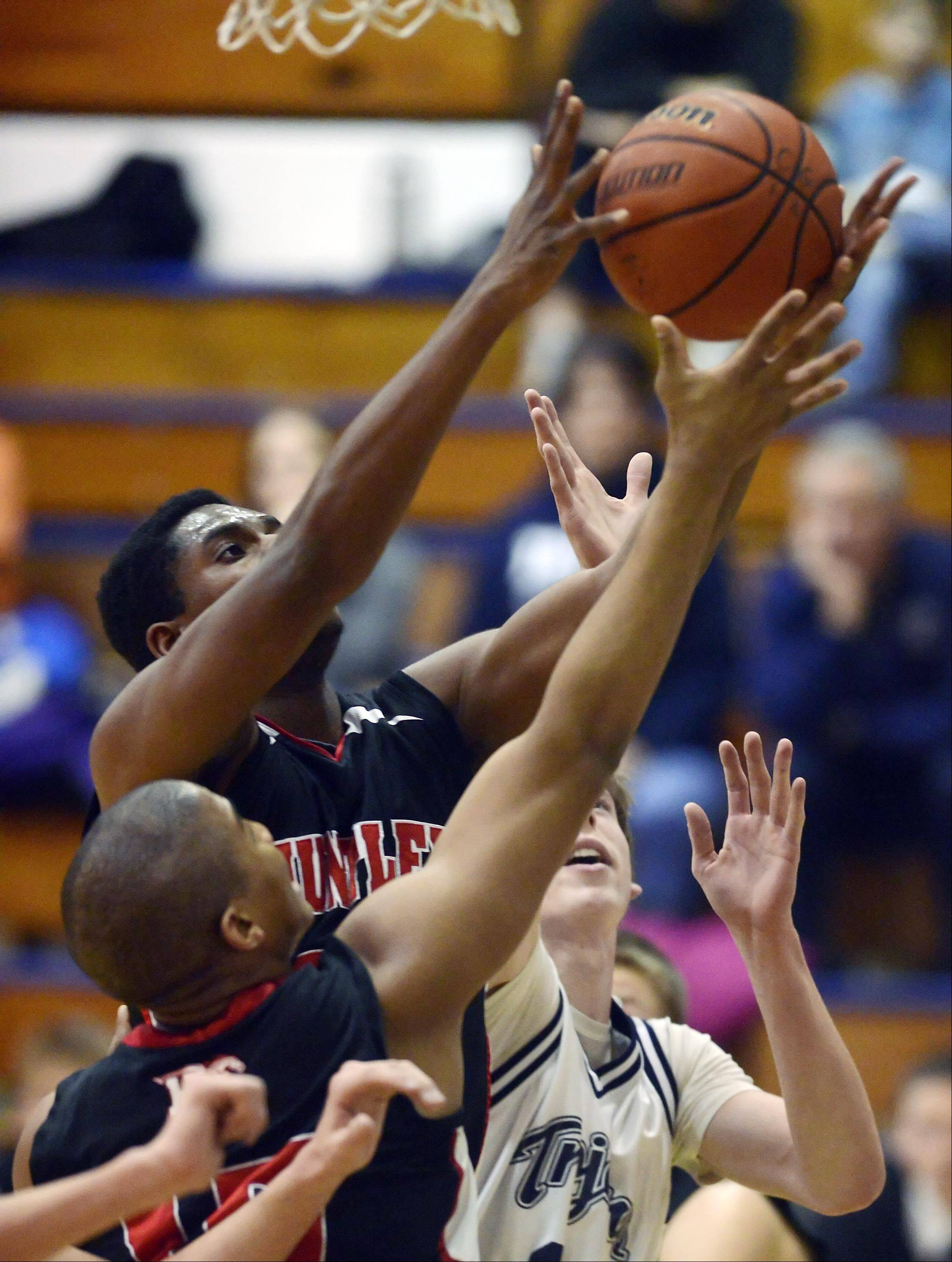 Huntley's Amanze Egekeze takes a rebound against teammate Bryce Only and Cary-Grove's Dean Lee Tuesday in Cary.