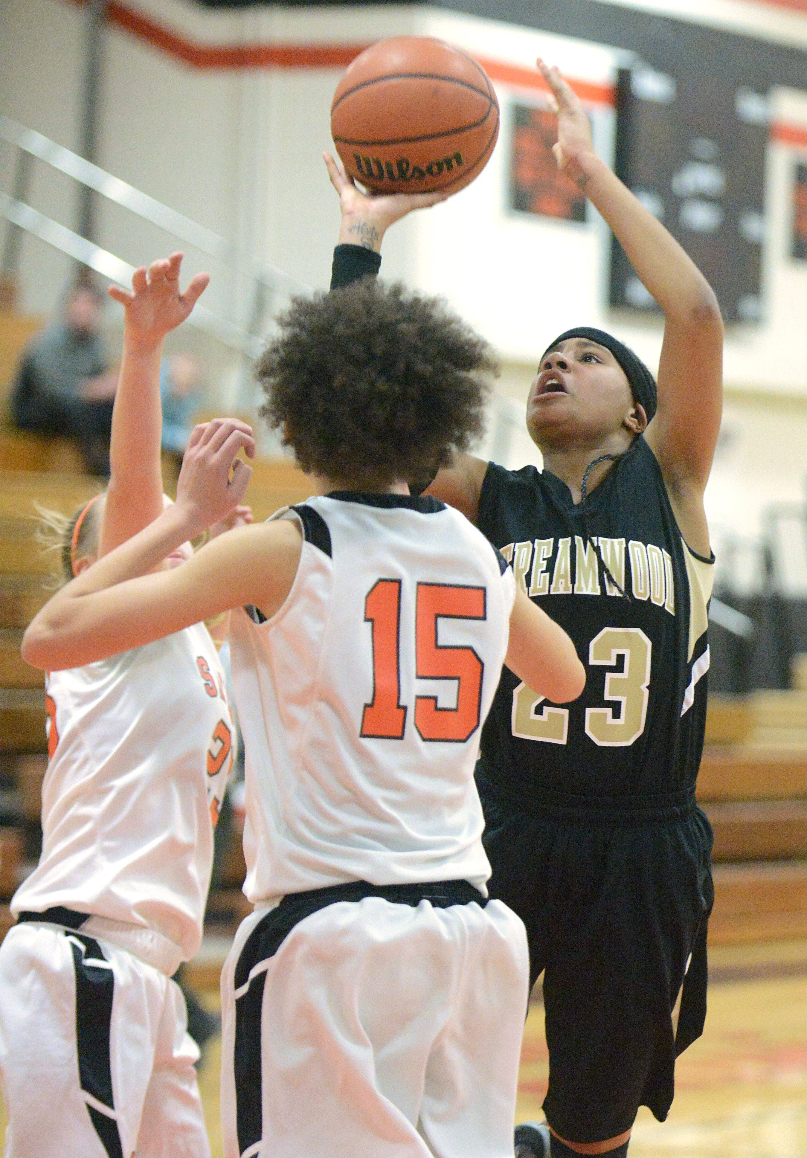 Streamwood�s Deja Moore shoots past a block by St. Charles East�s Amanda Hilton, left and Kyra Washington in the second quarter on Tuesday, January 22.