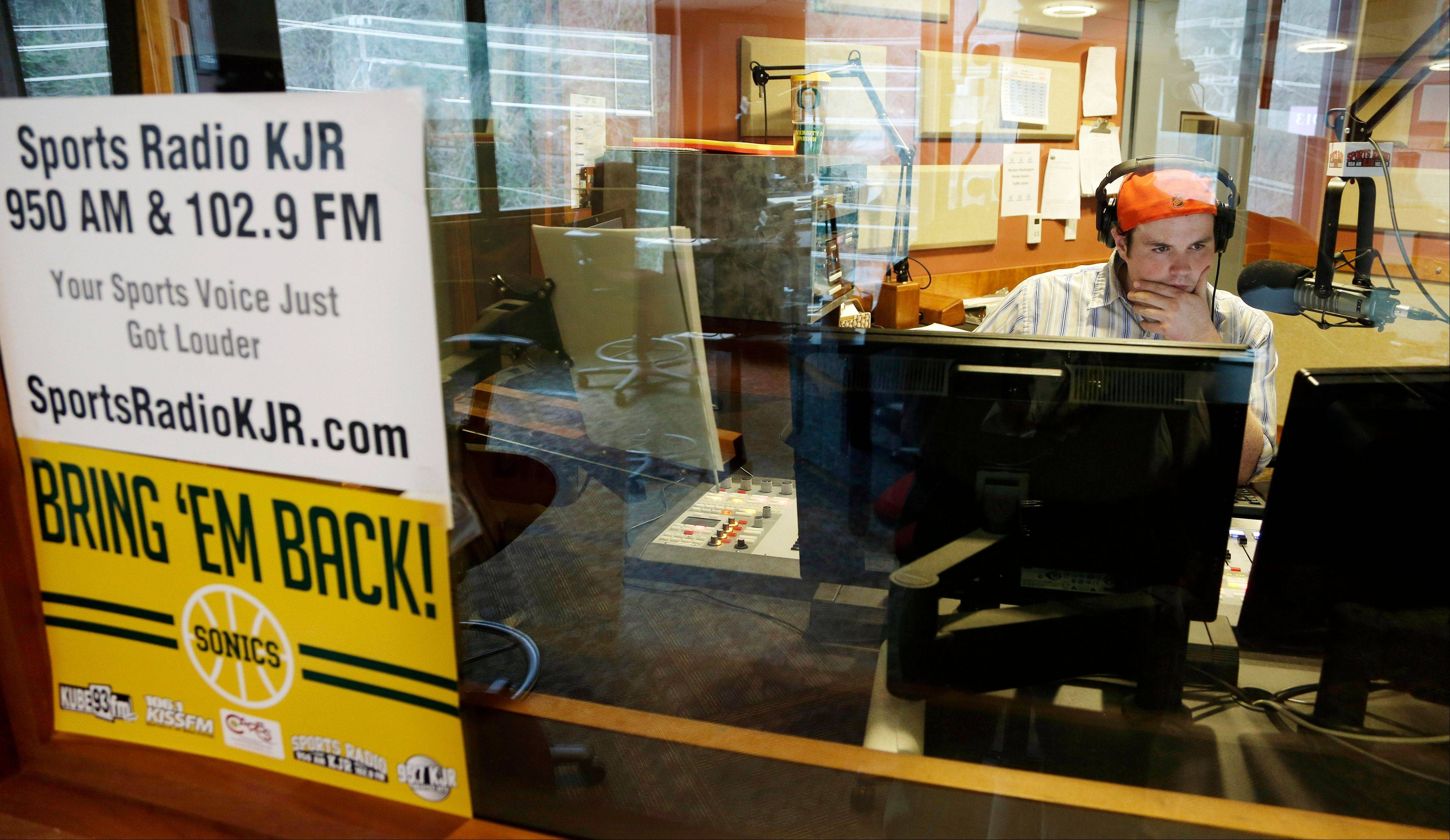 "Kevin Shockey, producer of the Ian Furness Show, works in a radio booth at sports radio station KJR in Seattle, Monday, Jan. 21, 2013, next to a sign that reads ""Bring 'Em Back!"" in reference to the Seattle SuperSonics NBA basketball team, which were sold and moved to Oklahoma City in 2008. Phone lines at the station were full as fans reacted to the news that the Maloof family, owners of the Sacramento Kings, had agreed to sell the team to a Seattle group led by investor Chris Hansen."