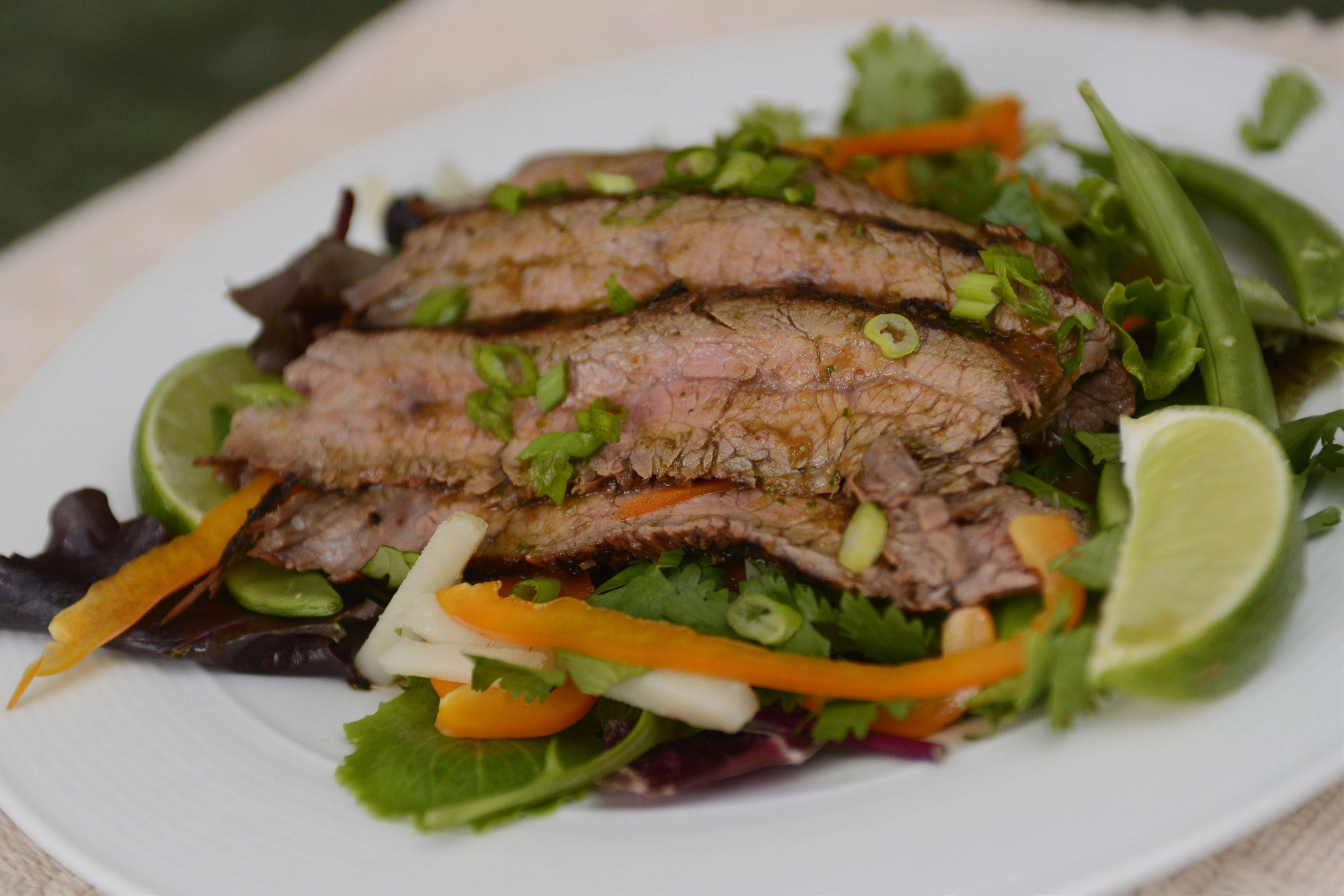 Slices of grilled, marinated flank steak top Ethan Danstrom's Asian-style dinner salad.