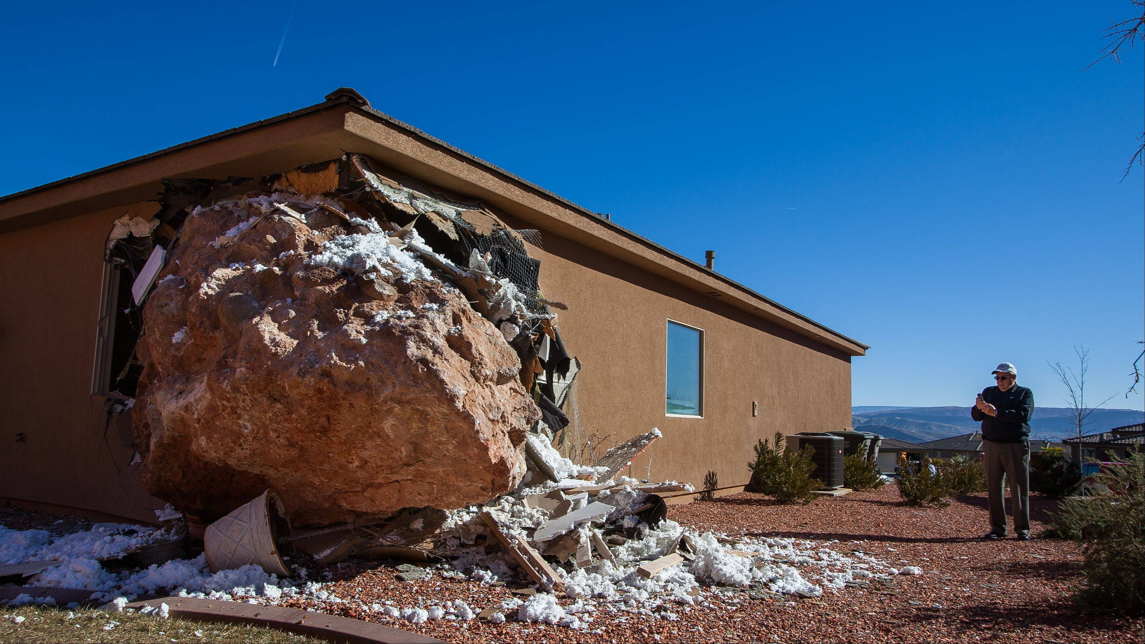 A bystander photographs a 12-by-9-foot boulder as it rests in the master bedroom of a home in St. George, Utah.