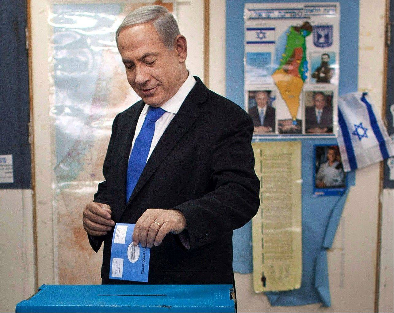 Israeli Prime Minister Benjamin Netanyahu casts his ballot, together with his wife Sara, left, and sons Yair and Avner, background left, at a polling station in Jerusalem on Tuesday.