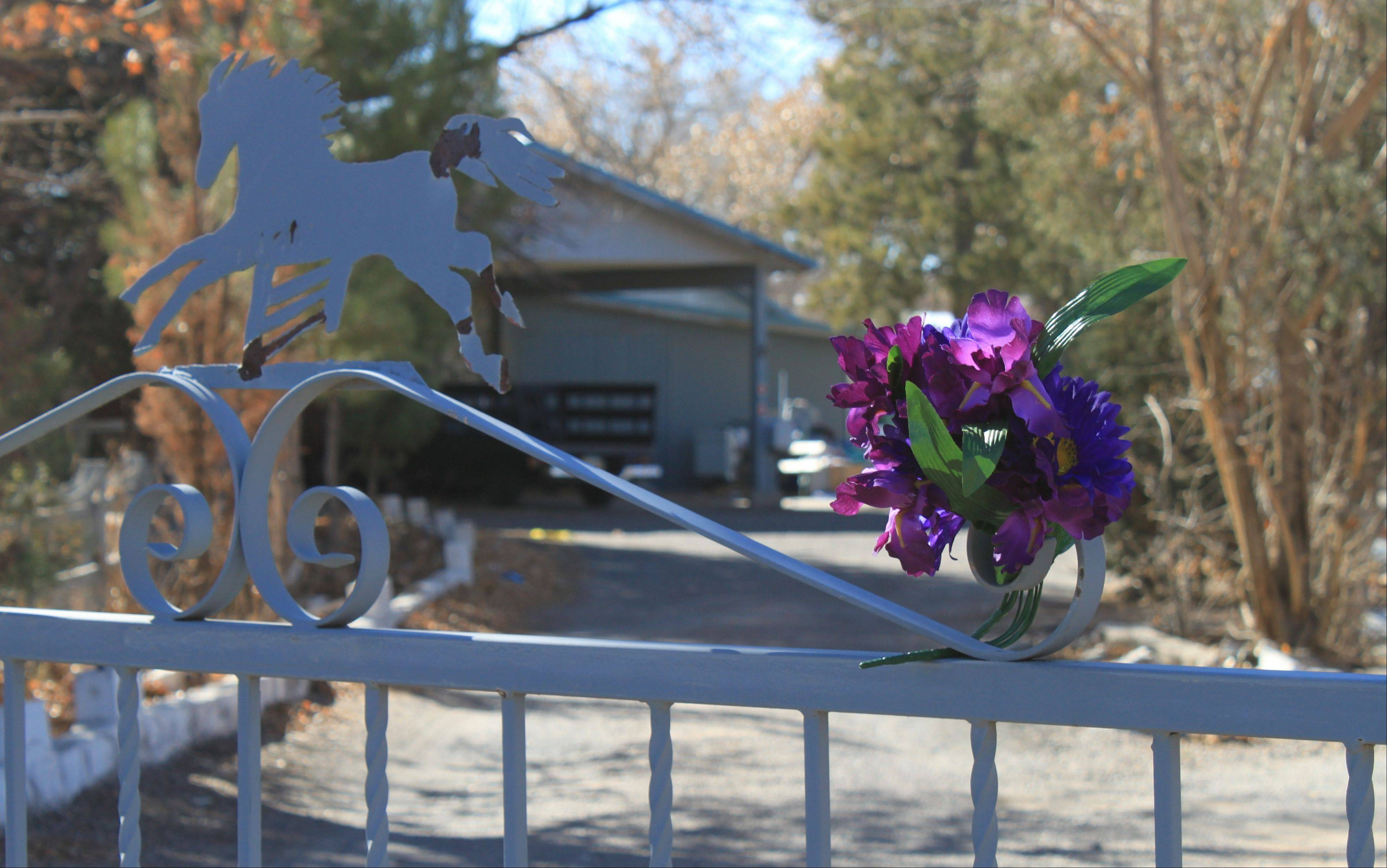 A bouquet of flowers adorns the entrance to a home on Monday, where a couple and their three young children were found shot to death south of Albuquerque, N.M. The couple's 15-year-old son is facing counts of murder and child abuse in connection with the shootings.