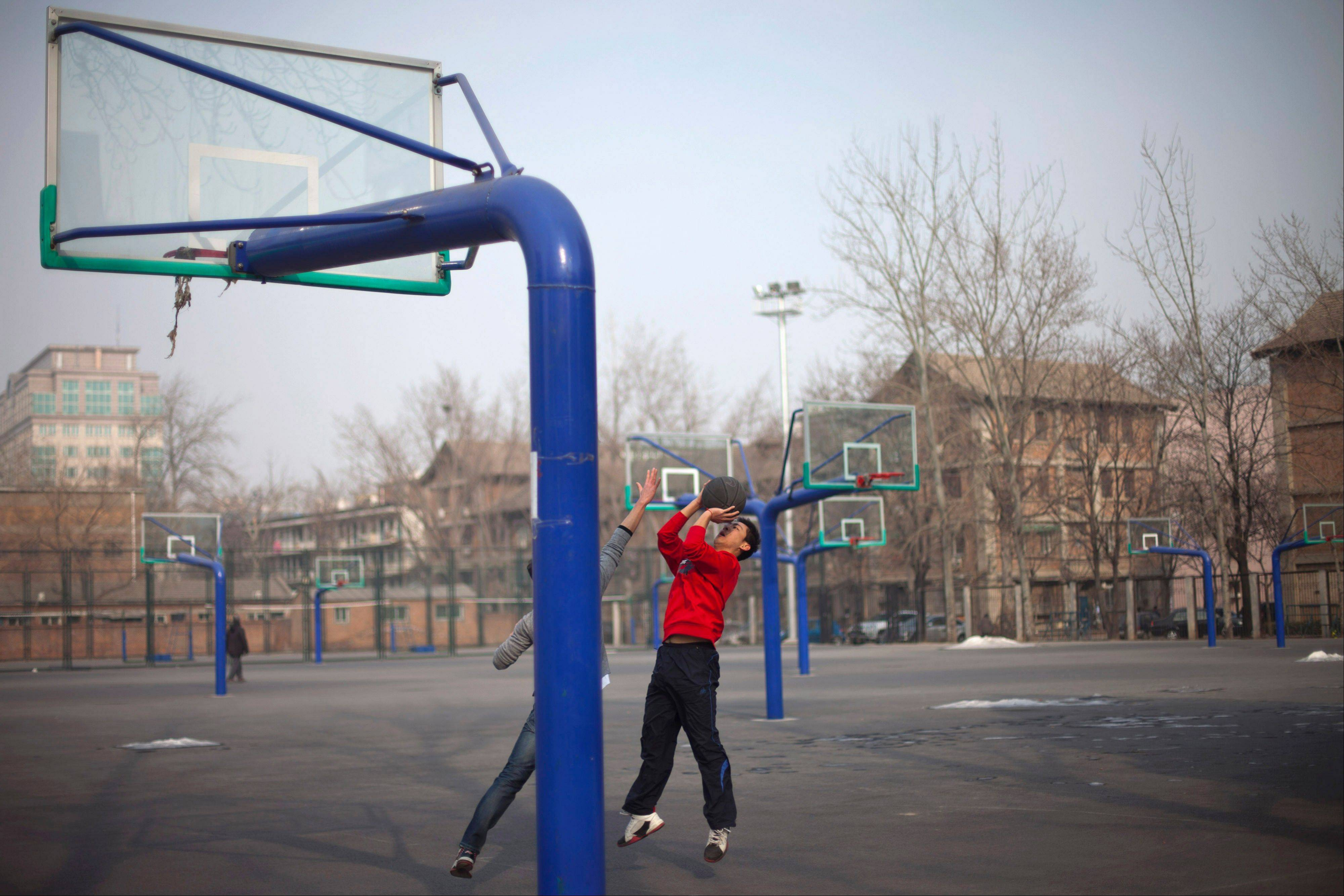 In this Saturday, Jan. 19, 2013 photo, students play basketball at their college's court in Beijing. Despite its formidable performance in recent Olympic Games, China has found itself in a crisis of declining fitness among its youngsters.