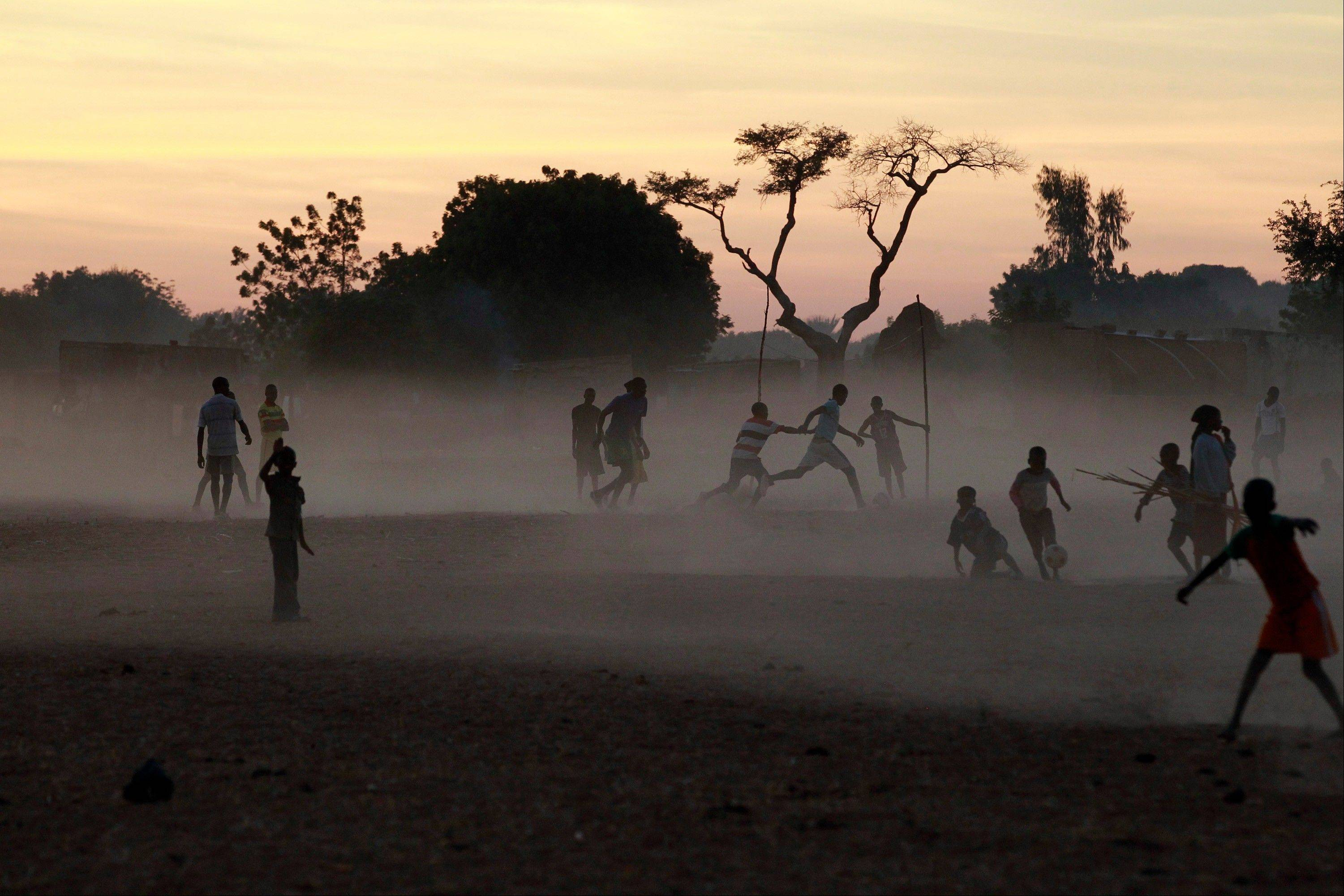 Children and adults alike play soccer on a dusty field in Segou, central Mali, some 240 km (140 miles) from Bamako Monday Jan. 21, 2013. French troops in armored personnel carriers rolled through the streets of Diabaly on Monday, winning praise from residents of this besieged town after Malian forces retook control of it with French help a week after radical Islamists invaded. The Islamists also have deserted the town of Douentza, which they had held since September, according to a local official who said French and Malian forces arrived there on Monday as well.