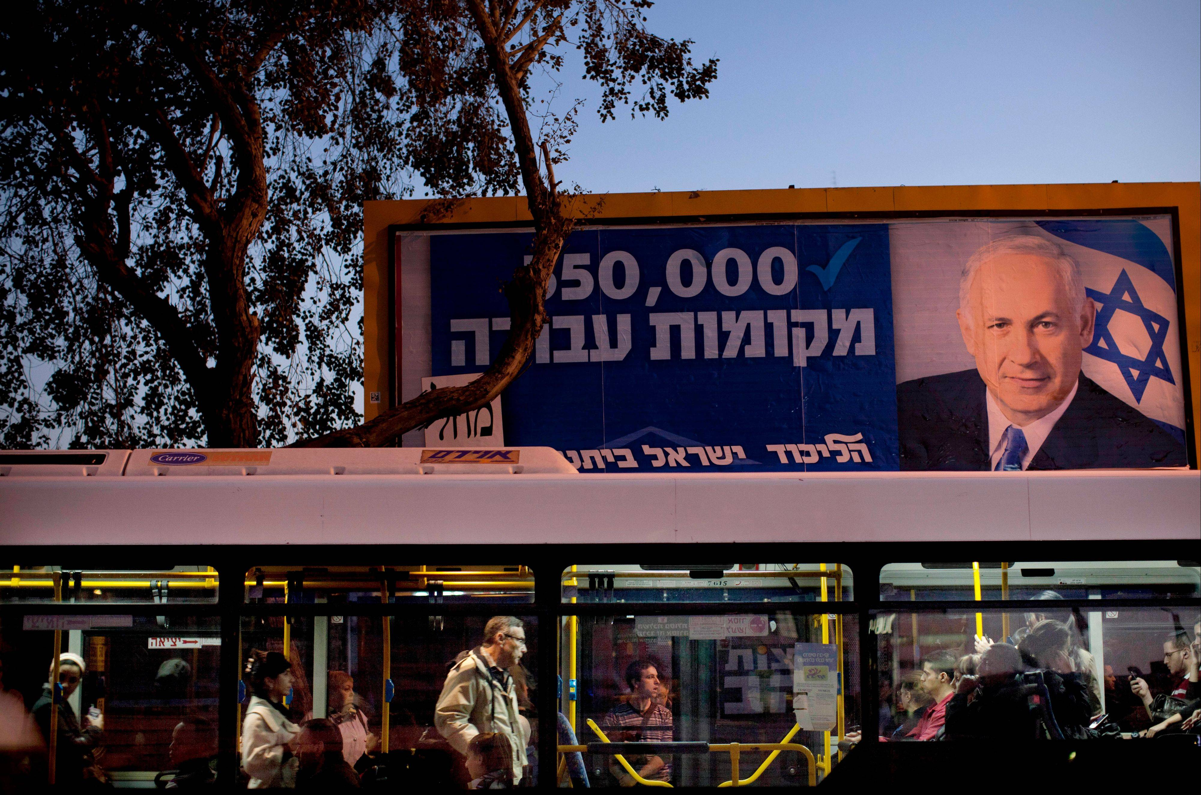 "A bus drives past an election campaign billboard of Israeli Prime Minister and Likud Party leader Benjamin Netanyahu in the central Israeli city of Ramat Gan, Monday. The general elections were held Tuesday. Hebrew on the billboard reads, ""350,000 job positions."""
