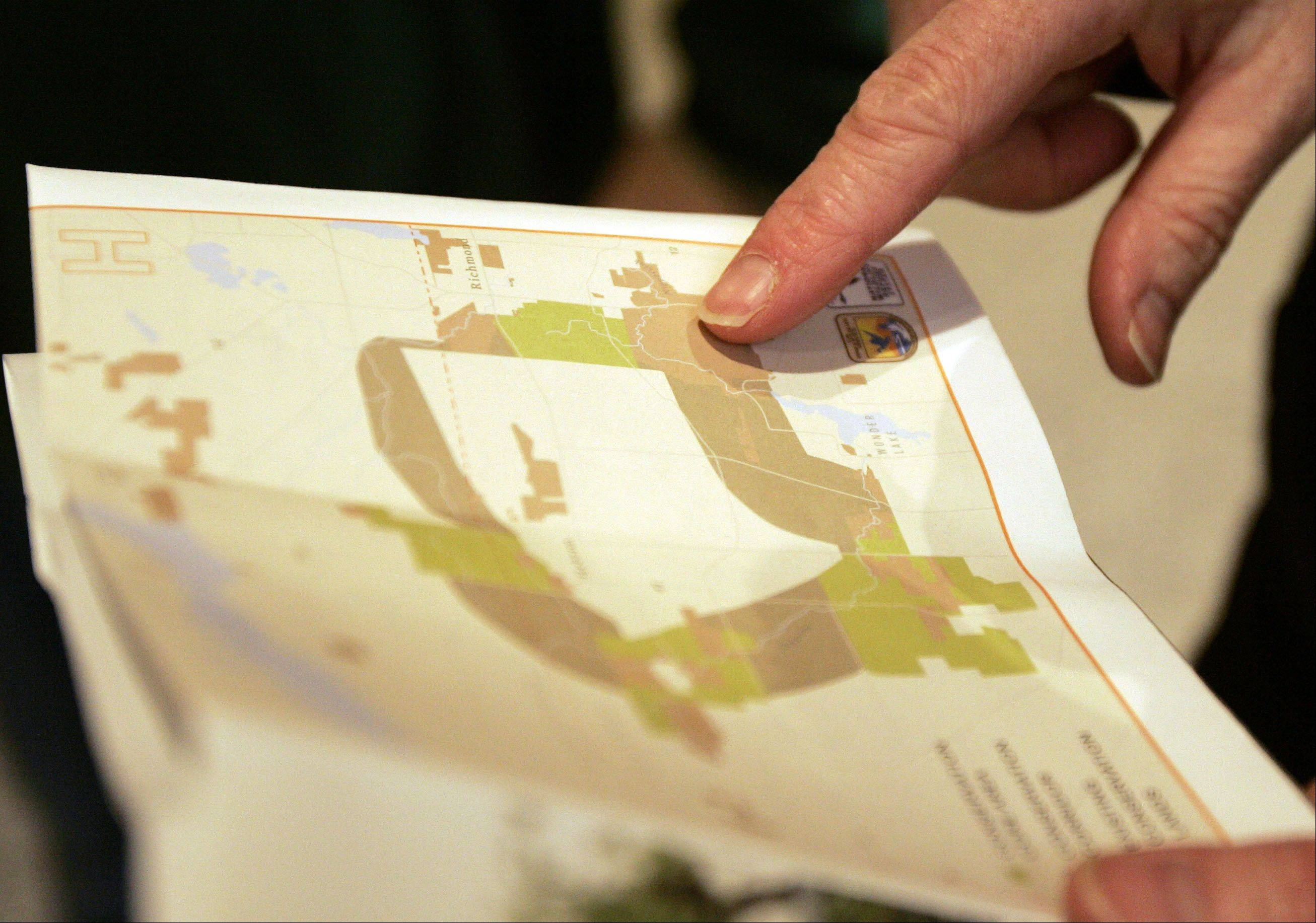 Lenore Beyer-Clow, policy director of Open Lands, looks over one of the maps with the new boundaries during a tour of Glacial Park and Hackmatack National Wildlife Refuge in McHenry County Friday.