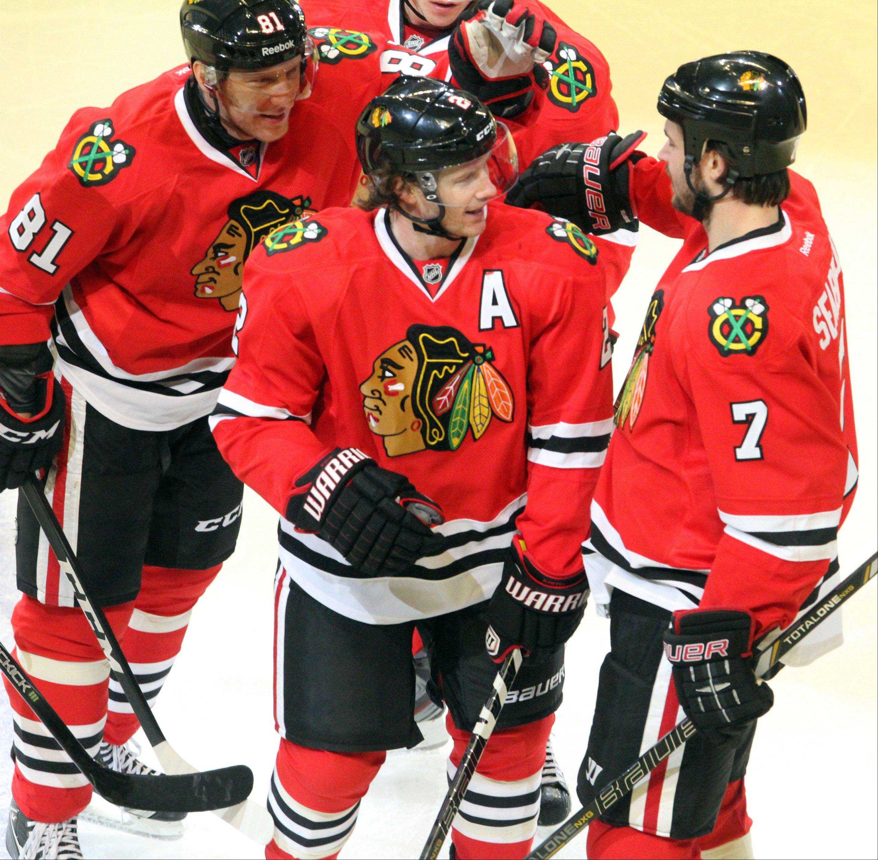 Blackhawks defenseman Duncan Keith gets a hand from teammates Marian Hossa, left, and Brent Seabrook his slap shot was deflected into the Blues' net by Seabrook to give the Hawks a 2-0 lead in the second period Tuesday night.
