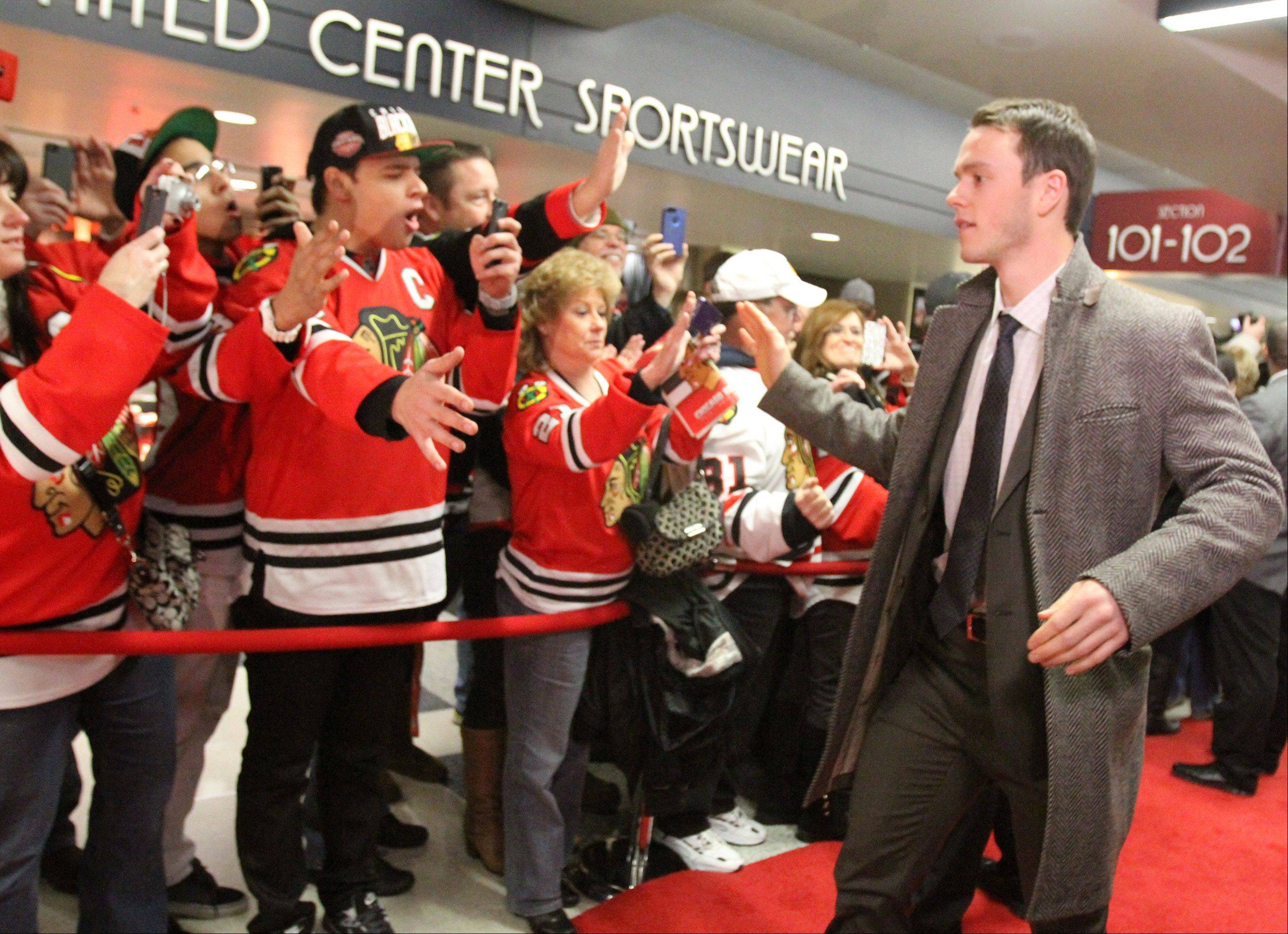 Chicago Blackhawks center Jonathan Toews high-fives fans at the team's red carpet event before the game.