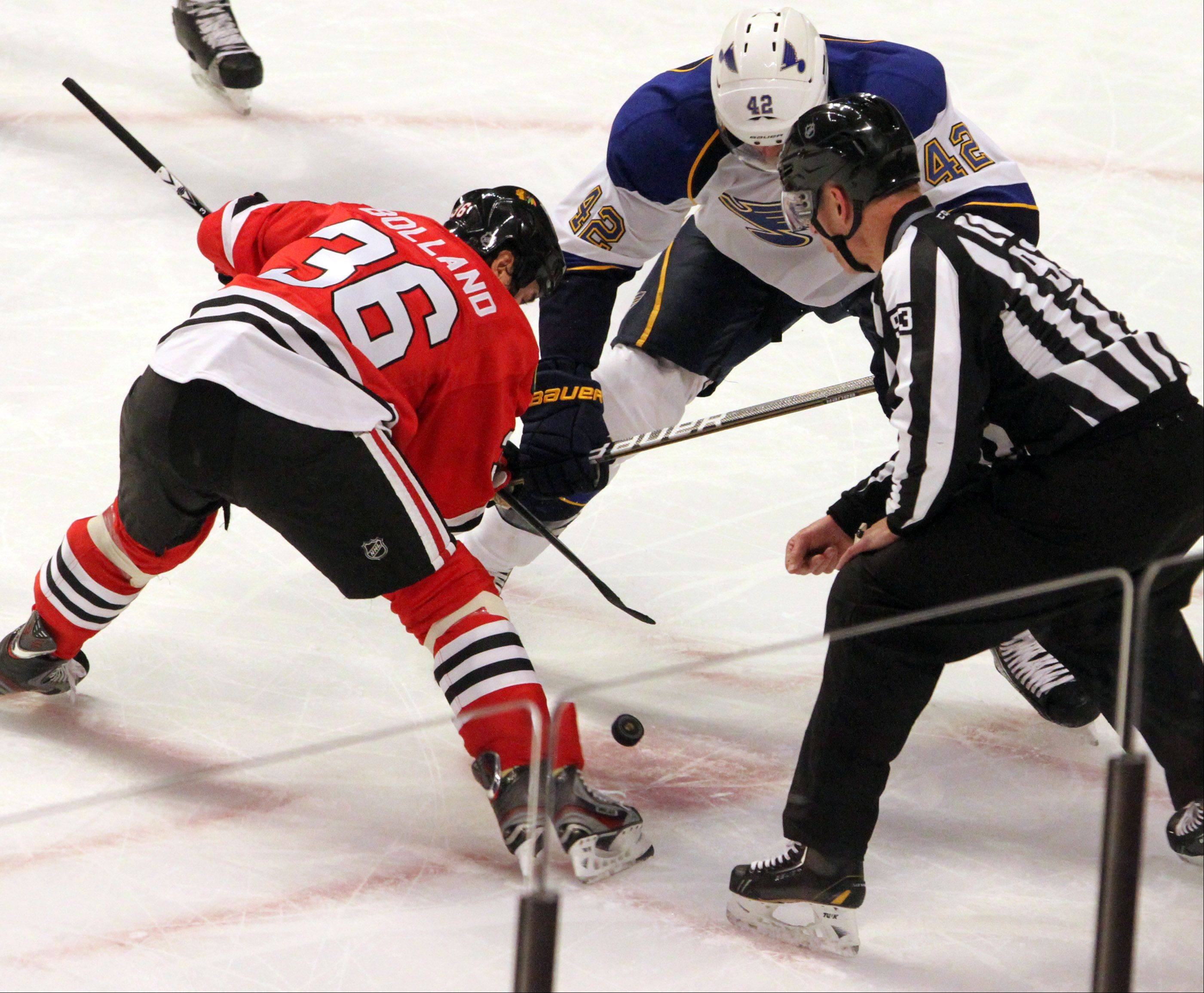 Chicago Blackhawks center Dave Bolland and St. Louis Blues center David Backes face off during the first period.