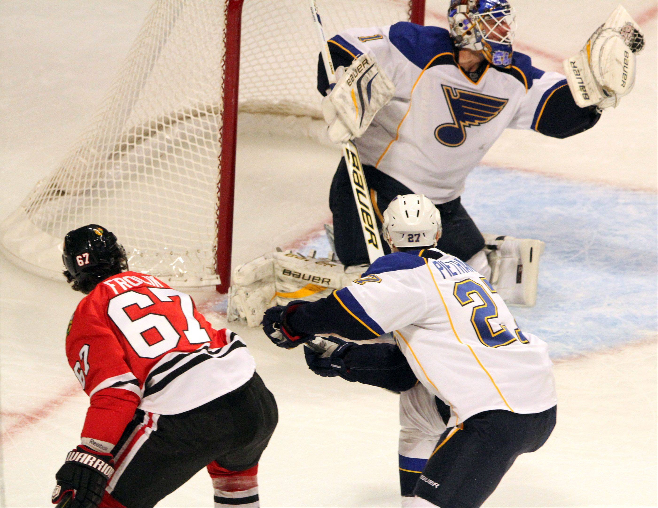 St. Louis Blues goalie Brian Elliott blocks a shot by Chicago Blackhawks center Michael Frolik during the second period.