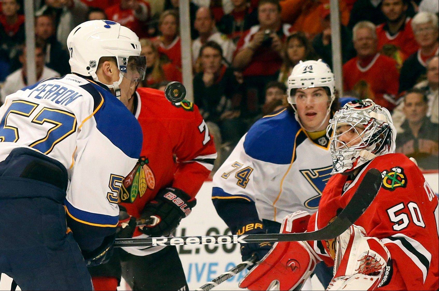St. Louis Blues left wing David Perron , right wing T.J. Oshie , and Chicago Blackhawks goalie Corey Crawford watch the puck during the first period.