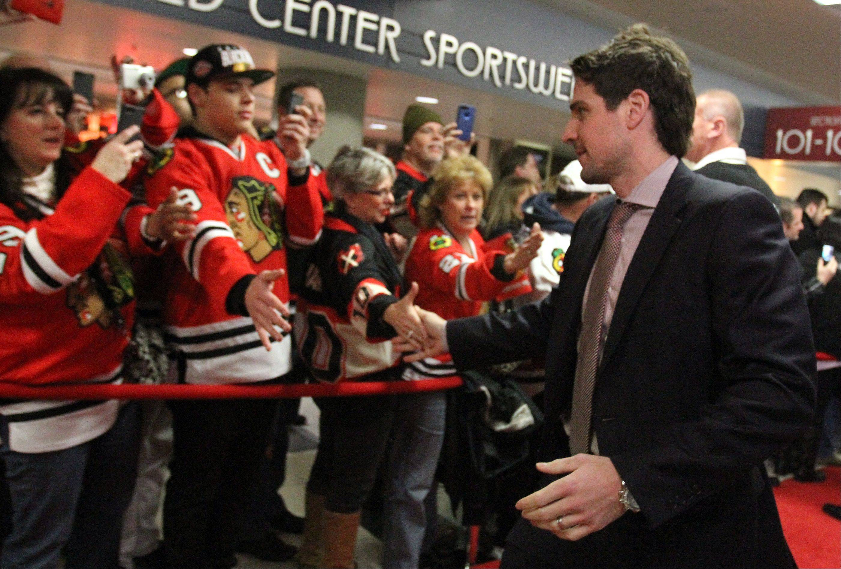 Chicago Blackhawks center Patrick Sharp high-fives fans at the team's red carpet event before the home opener.