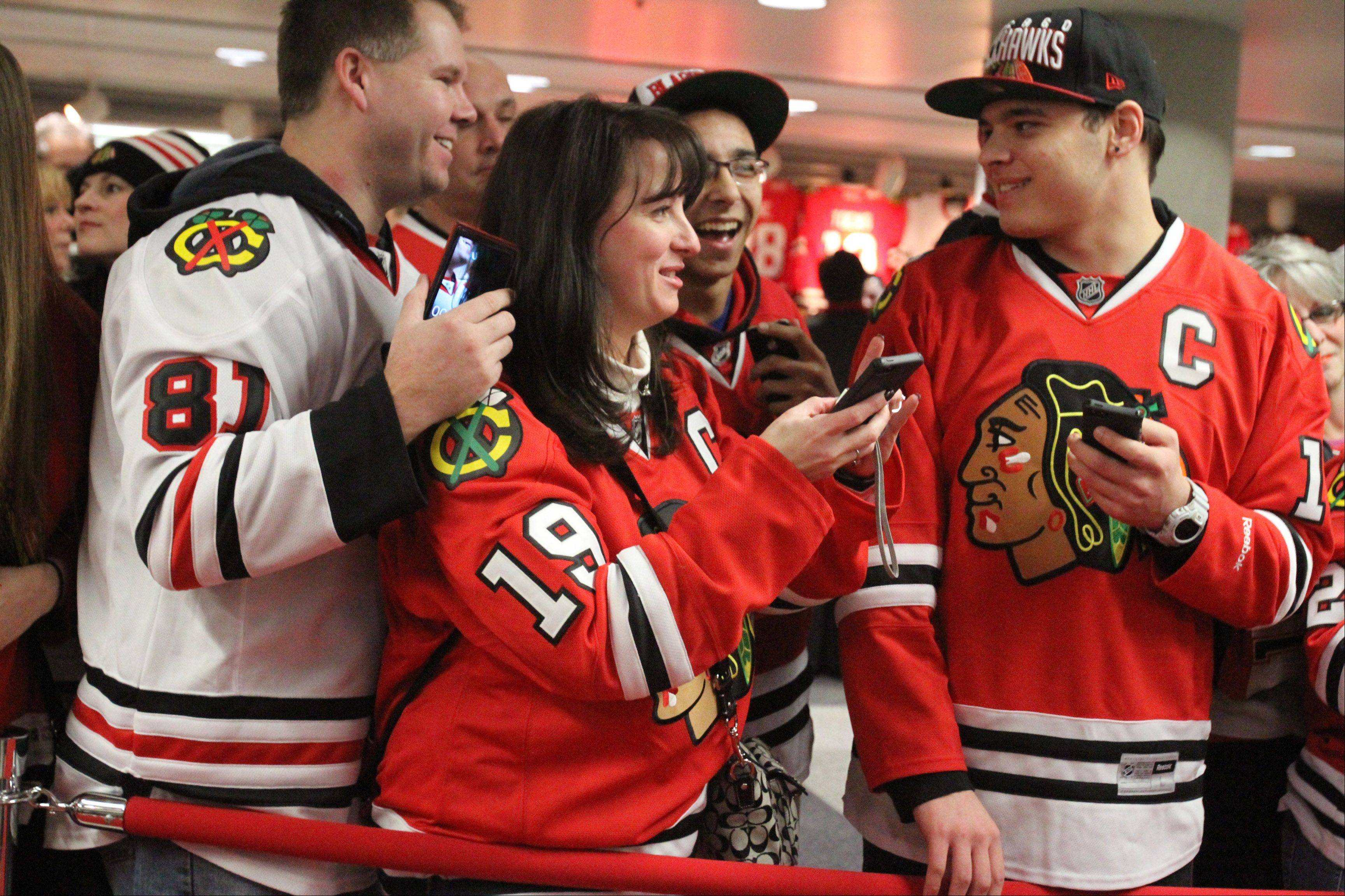 Chicago Blackhawks fans look at smartphone photograph during the red carpet event before the home opener.