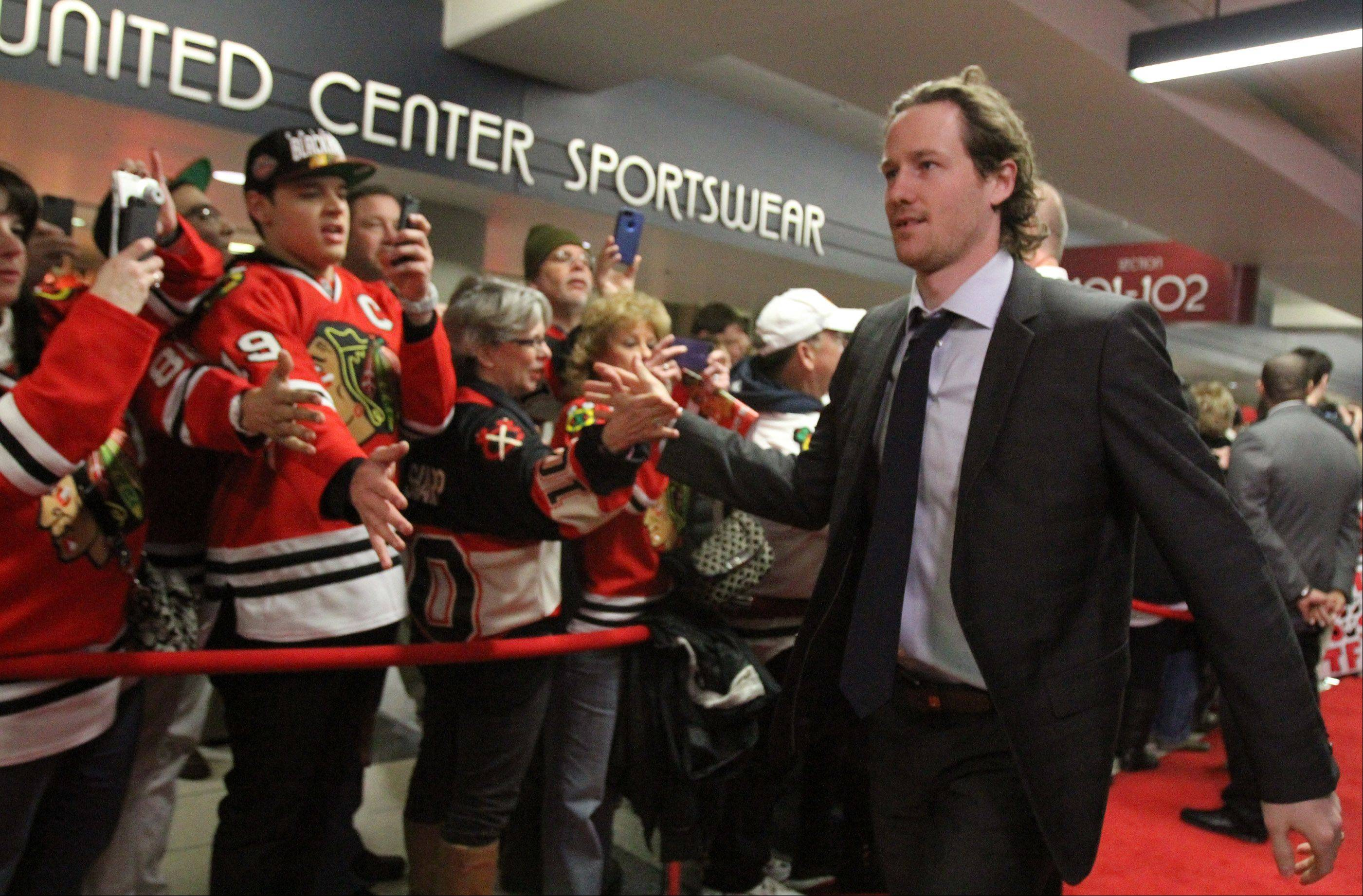 Chicago Blackhawks defenseman Duncan Keith high-fives fans at the team's red carpet event before the home opener.