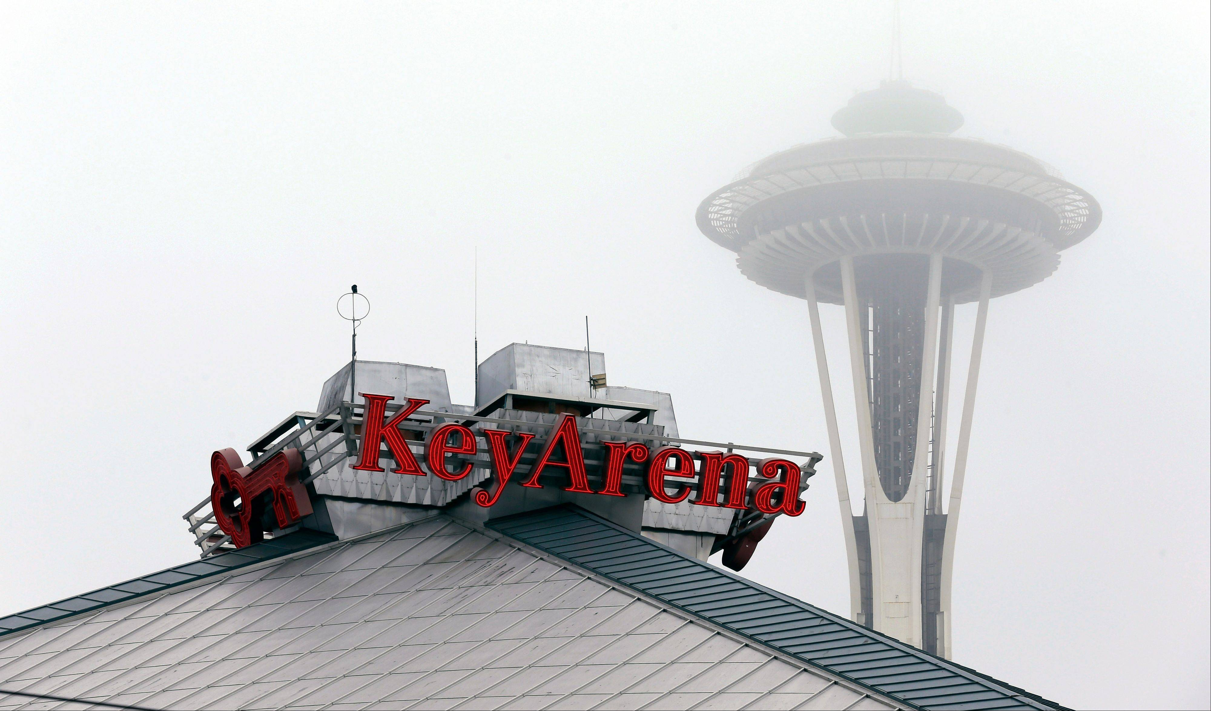 A sign for KeyArena appears near the Space Needle, Monday, Jan. 21, 2013, in Seattle. KeyArena would host NBA basketball games for two seasons if a team returns to Seattle as was reported likely on Monday, while a new permanent facility is built south of downtown Seattle. The Maloof family has agreed to sell the Sacramento Kings to a Seattle group led by investor Chris Hansen, the league confirmed in a statement Monday morning.
