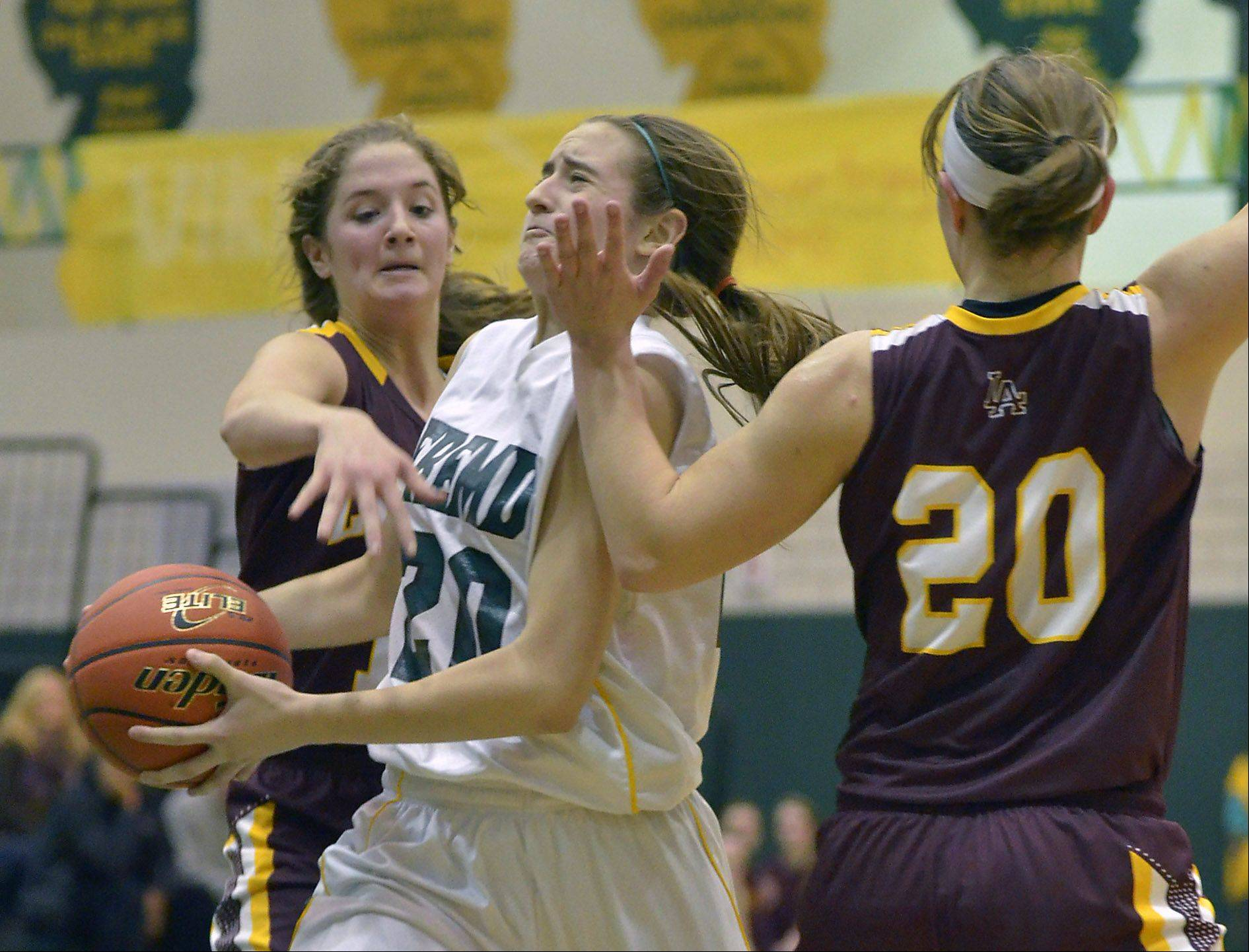 Fremd's Haley Gorecki, 20, draws a foul from Loyola Academy's Maggie Nick, 12, and Egan Berne, 20, Monday.