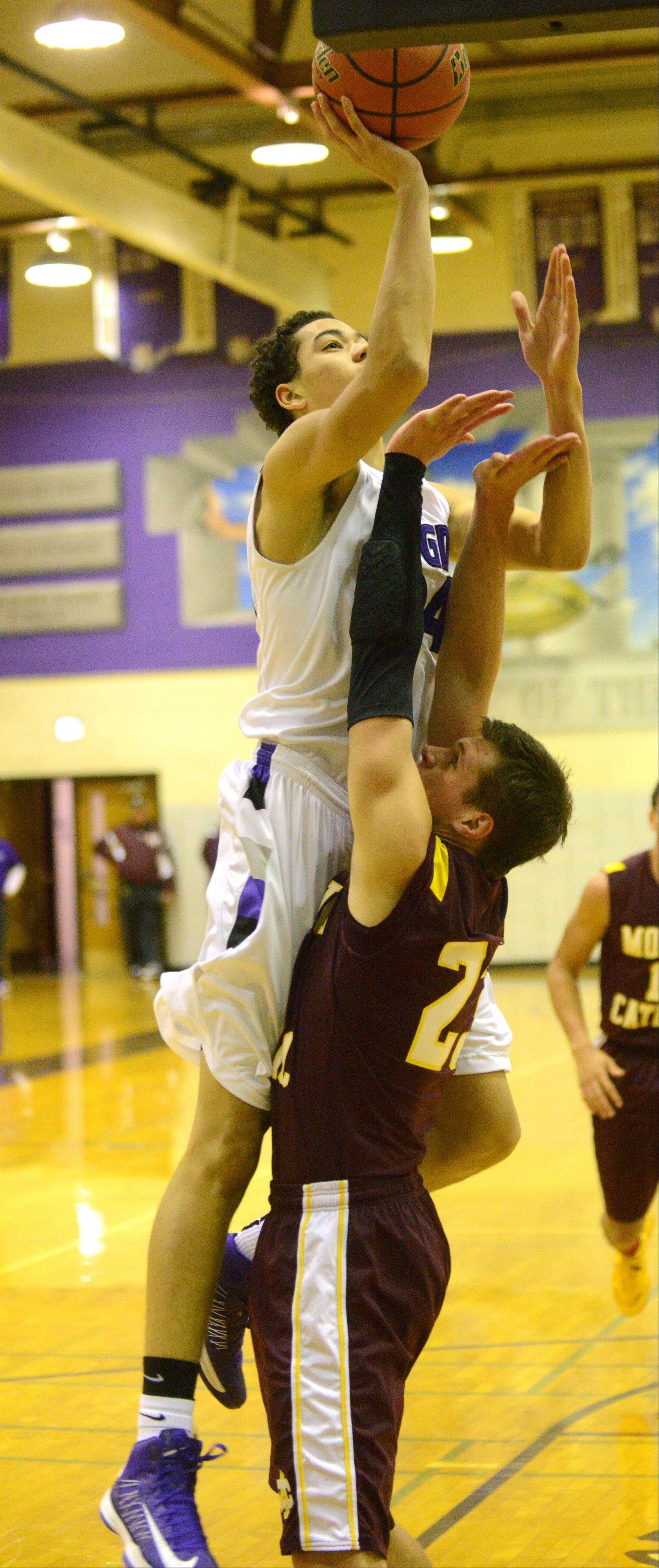 Downers Grove North's Nick Norton, left, takes a shot over Montini's Matt Brachmann Wednesday's basketball game.