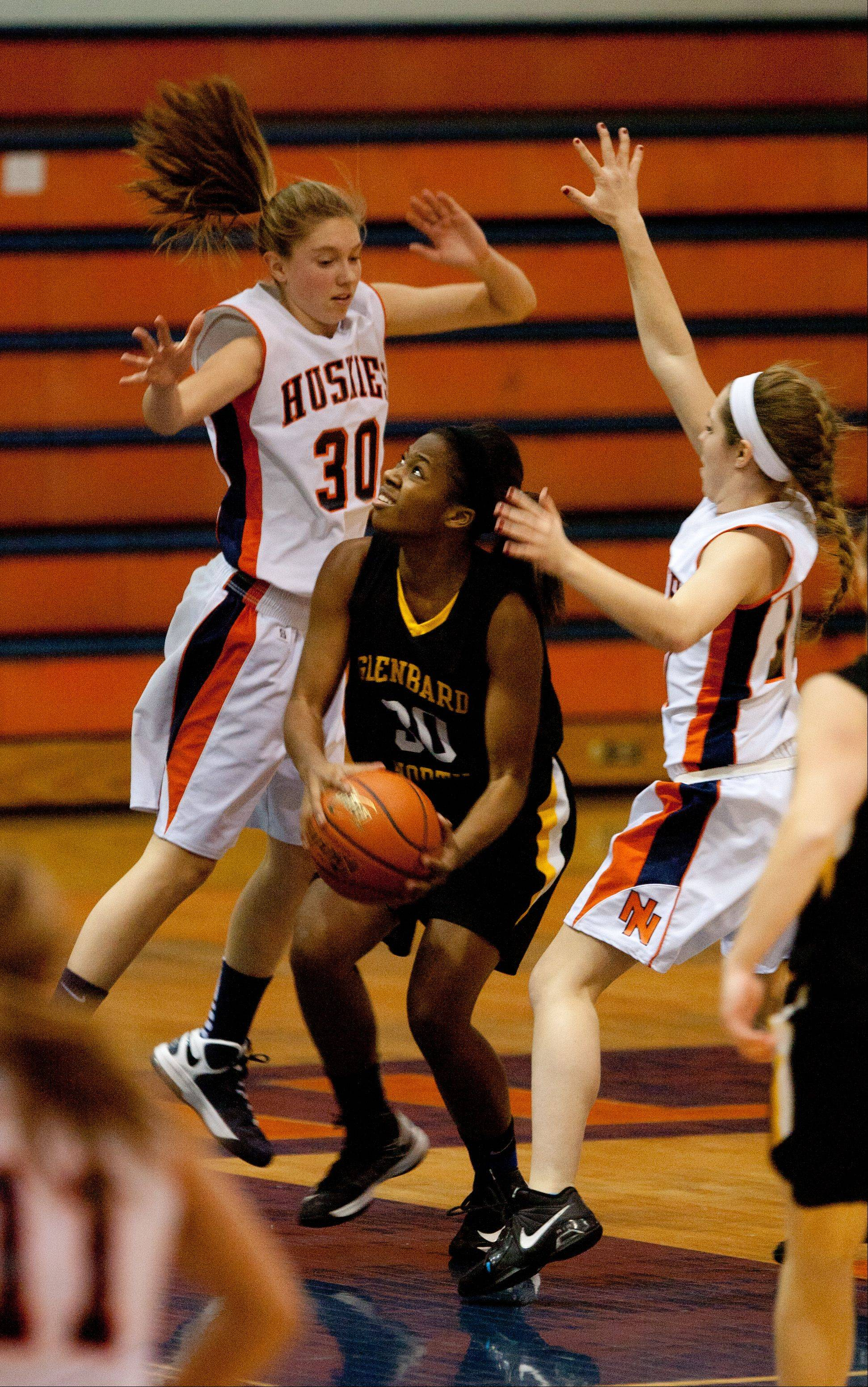 Glenbard North's, Laila Pickens, center, looks to shoot over Naperville North's Jenny Smith, 30, during Monday's game in Naperville.