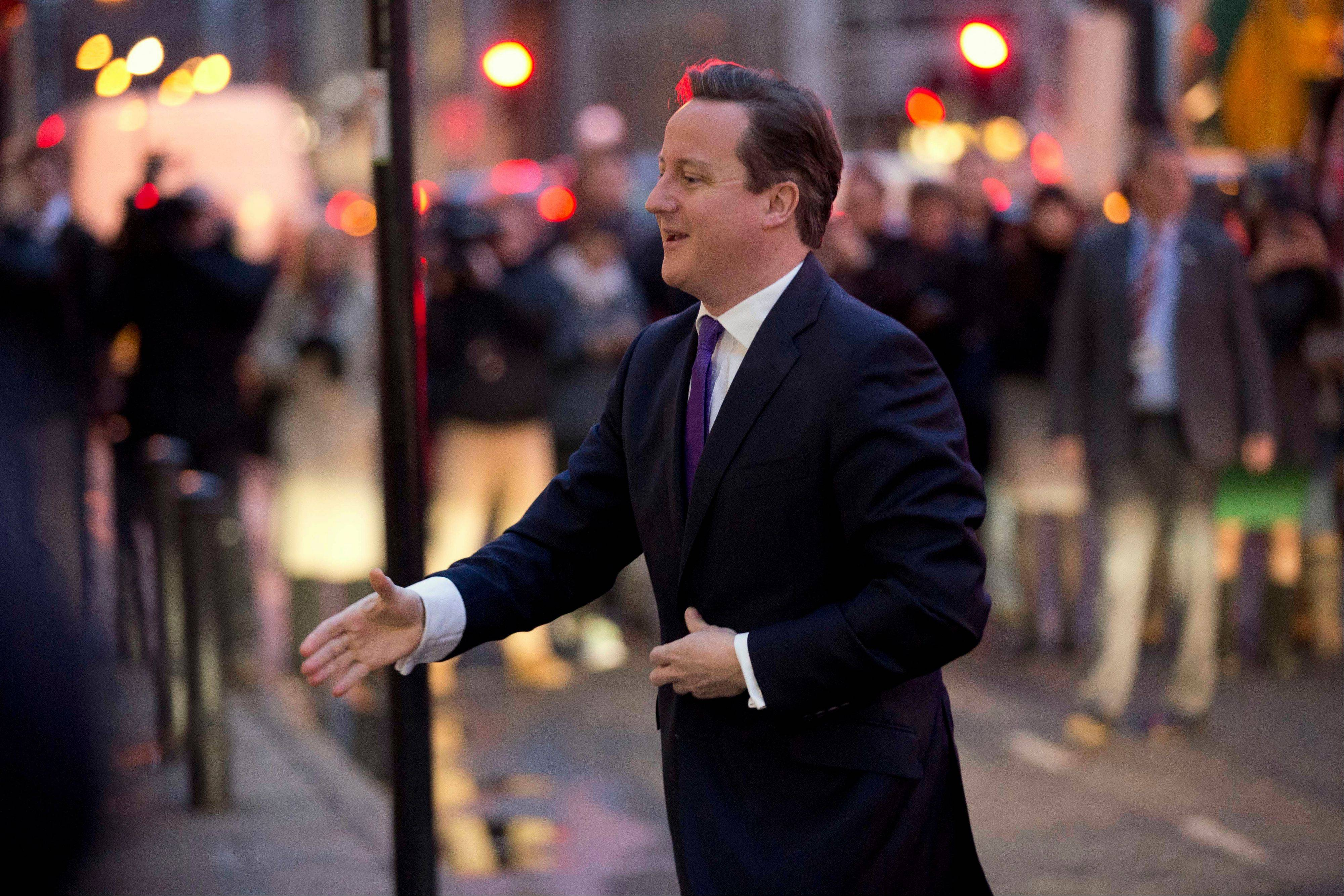 Britain�s Prime Minister David Cameron reaches out to shake hands as he is greeted upon his arrival to deliver a speech on holding a referendum on staying in the European Union in London, Wednesday.