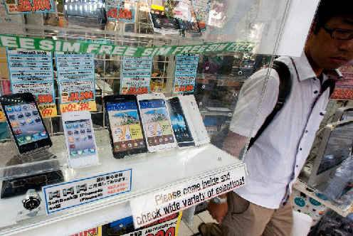 Apple Inc. iPhones, left, and Samsung Electronics Co. Galaxy smartphones at an electronics store in Tokyo,