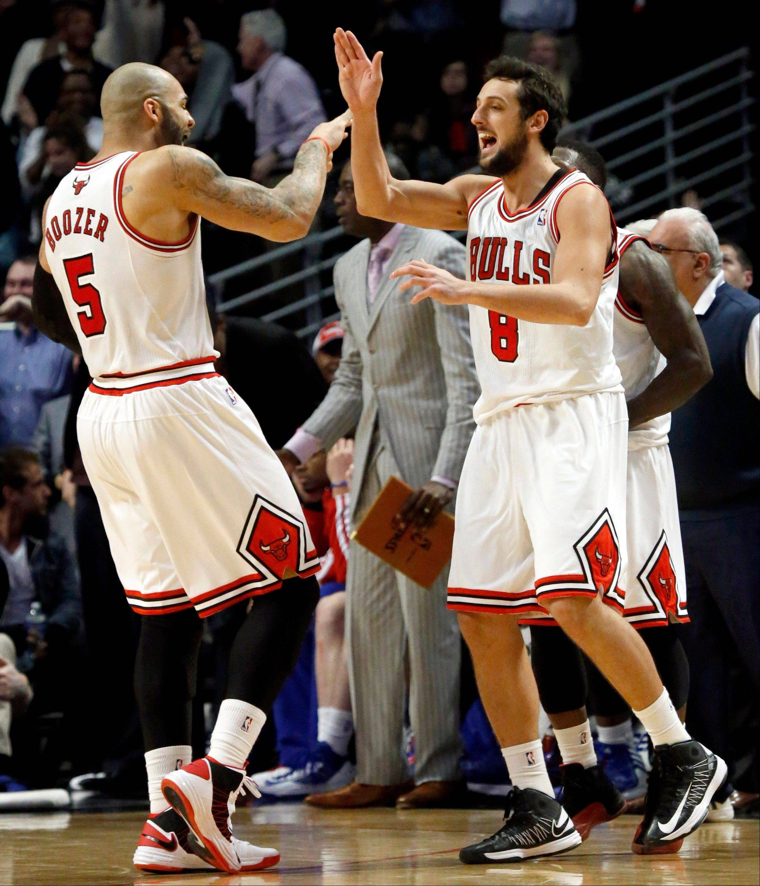 Chicago Bulls guard Marco Belinelli (8) celebrates with Carlos Boozer after making the winning basket during the second half of an NBA basketball game Wednesday against the Detroit Pistons in Chicago. The Bulls won 85-82.