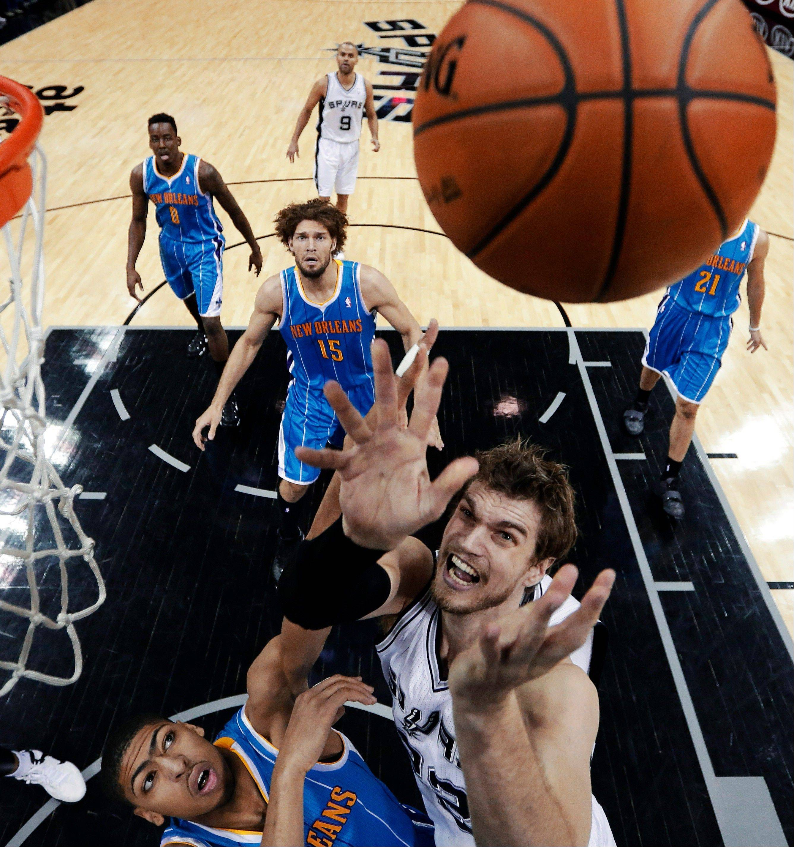 New Orleans Hornets� Anthony Davis, bottom left, and San Antonio Spurs� Tiago Splitter, bottom right, of Brazil, reach for a rebound during the first quarter of an NBA basketball game, Wednesday, Jan. 23, 2013, in San Antonio.