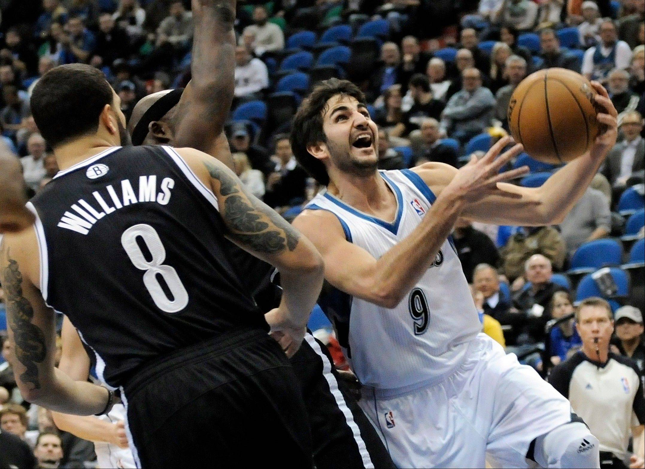 Minnesota Timberwolves� Ricky Rubio, right, of Spain, lays up past Brooklyn Nets� Deron Williams in the first half of an NBA basketball game on Wednesday, Jan. 23, 2013, in Minneapolis.