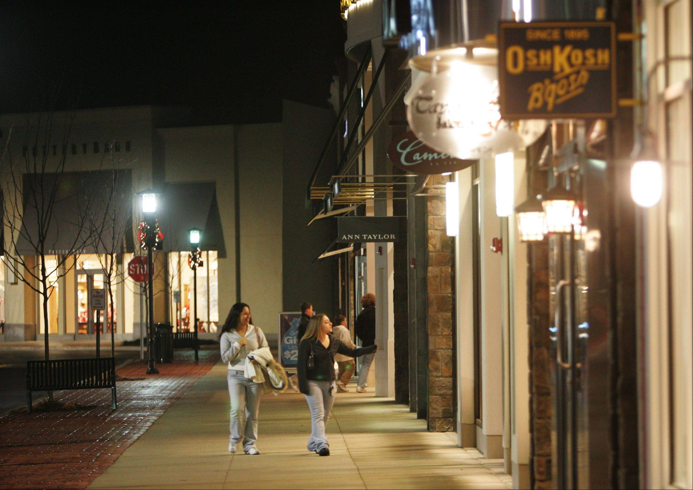 Shoppers stroll by shops at the Algonquin Commons, a shopping center in Algonquin the focus of a foreclosure lawsuit.