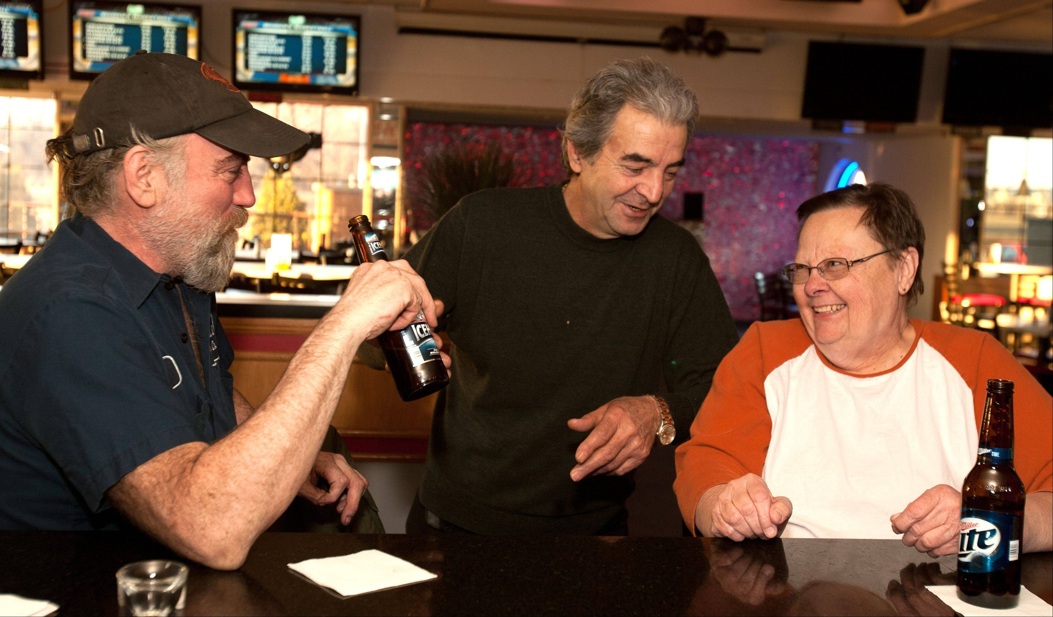 Shawn Farnand, left, Dennis Theros and Nancy Michalski share a laugh over drinks at Club Shotz in Carol Stream.