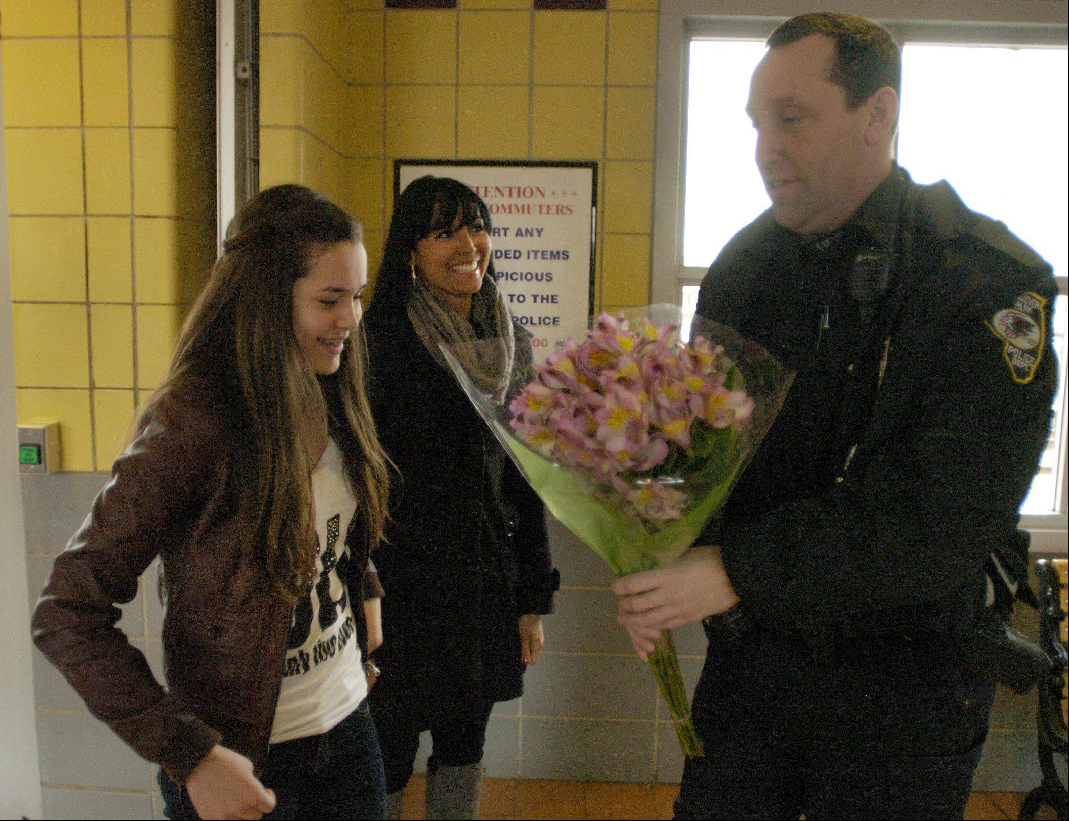 Hanover Park police Officer George Sullivan presents flowers to Brianna Elizondo of Carol Stream for her birthday. Sullivan helped deliver Brianna 13 years ago at the Metra station parking lot when labor went a bit too quickly for mother Monica Bakos.