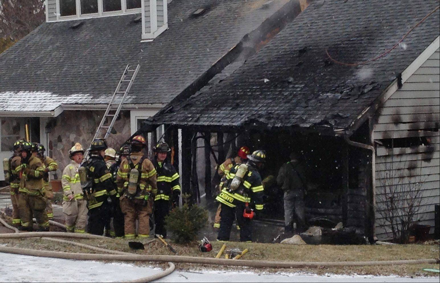 Firefighters inspect the fire damage in a garage attached to a home on the 26000 block of North Main Street in Wauconda early Wednesday afternoon.