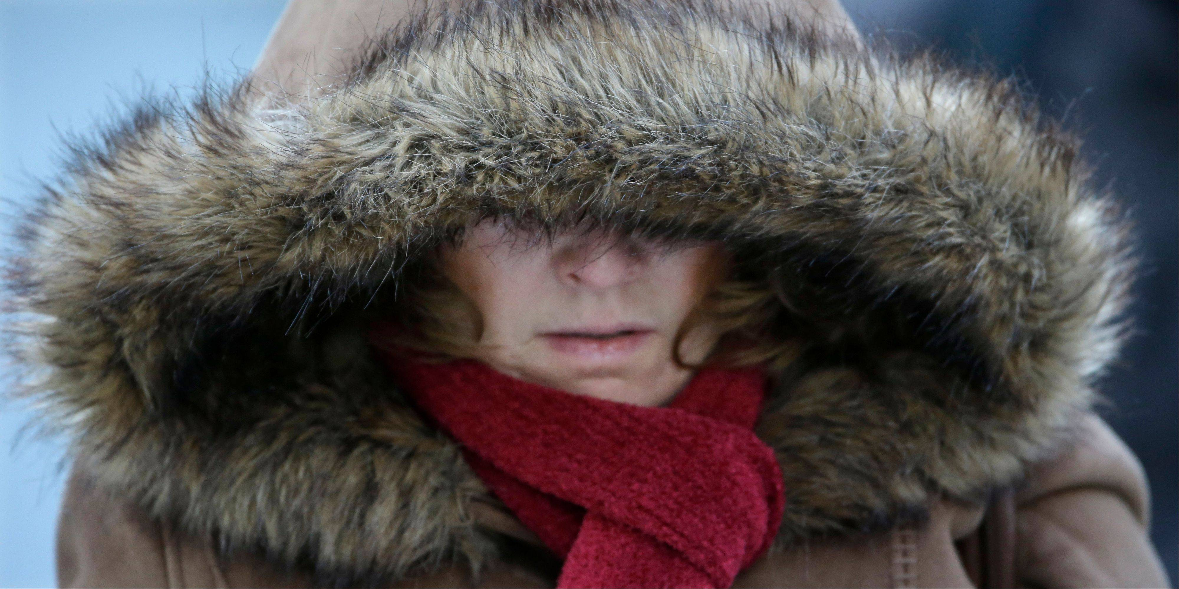 A commuter bundles up against extreme cold conditions Tuesday, Jan. 22, 2013, in Chicago.