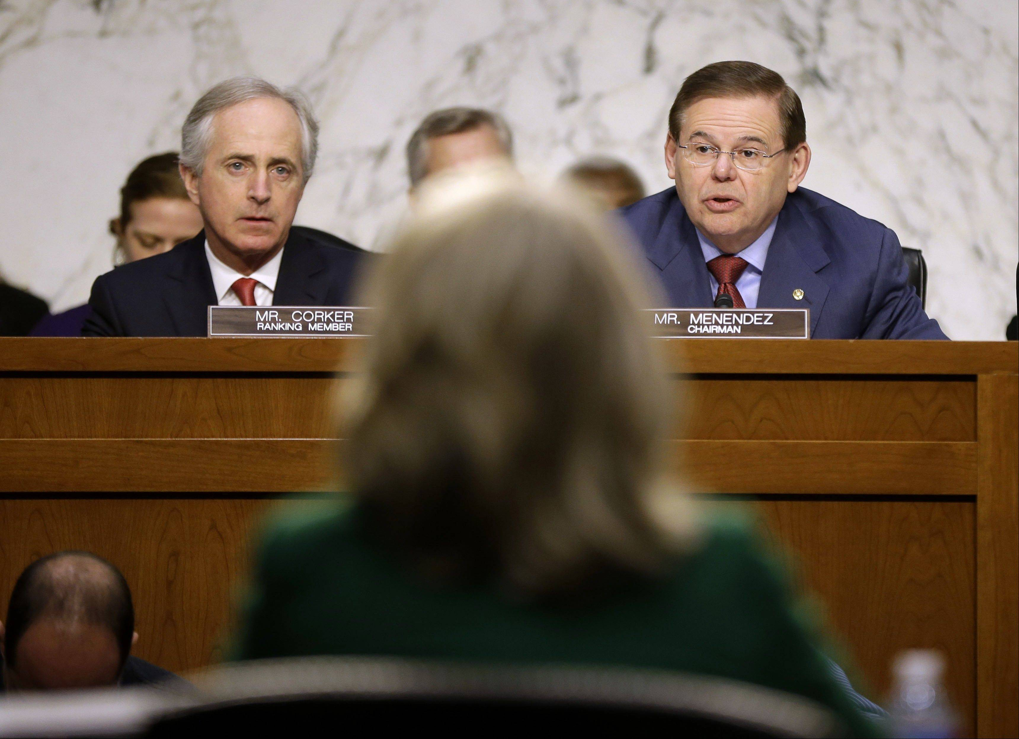 Secretary of State Hillary Rodham Clinton, center, back to camera, and the Senate Foreign Relations Committee ranking Republican Sen. Bob Corker, R-Tenn., left, listens as the committee's presiding Sen. Robert Menendez, D-N.J., speaks on Capitol Hill in Washington, Wednesday, Jan. 23, 2013, during the committee's hearing on the deadly September attack on the U.S. diplomatic mission in Benghazi, Libya, that killed Ambassador Chris Stevens and three other Americans.