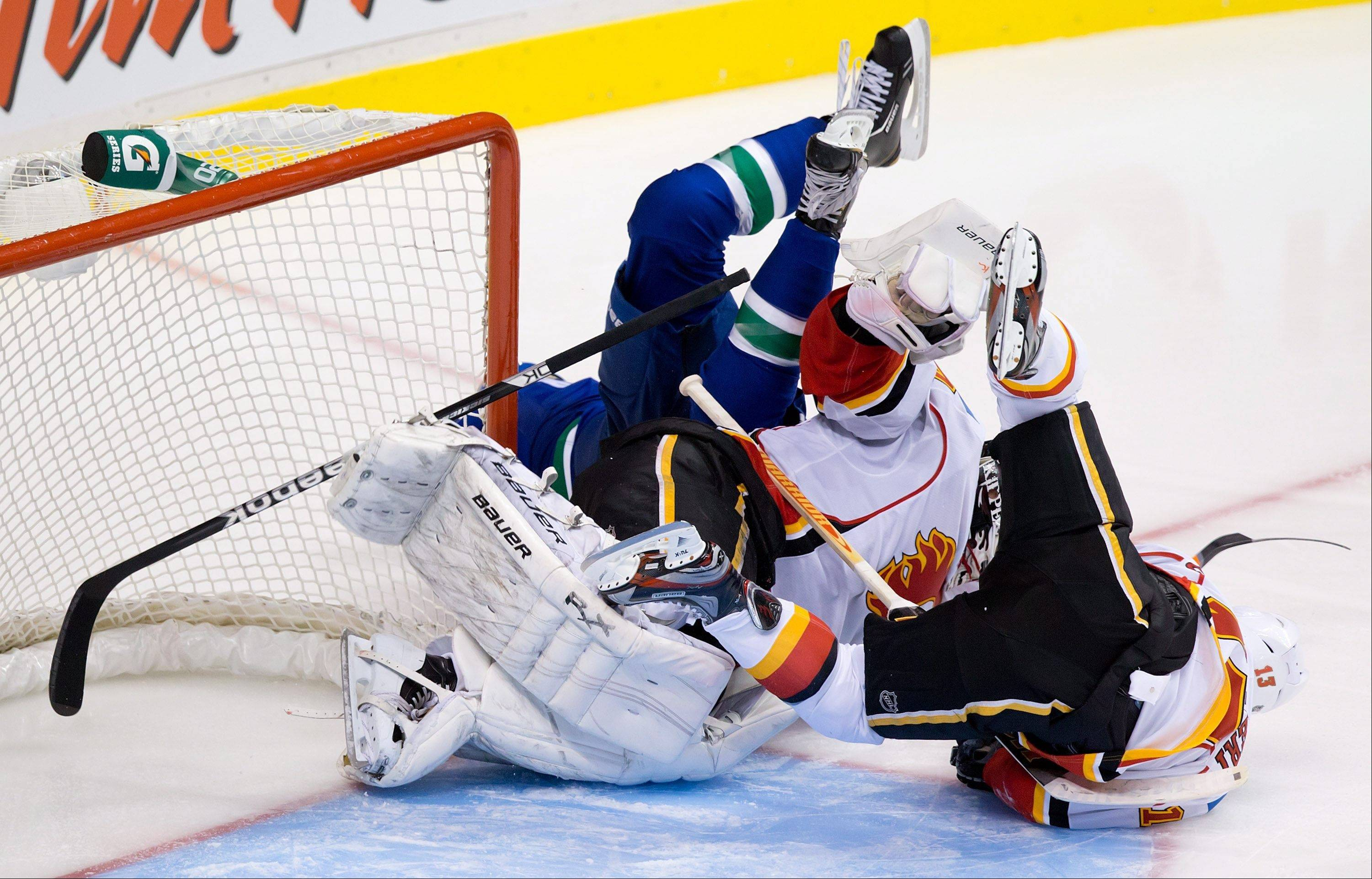Vancouver Canucks' Zack Kassian, left, crashes into Calgary Flames goalie Miikka Kiprusoff, of Finland, and Mike Cammalleri, right, during the third period of an NHL hockey game in Vancouver, British Columbia.